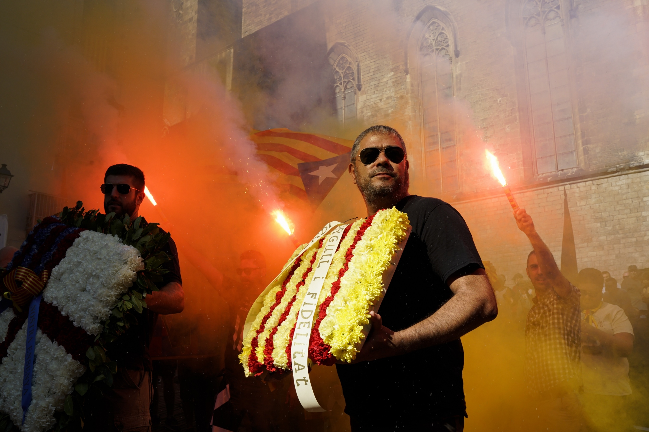 "(AP Photo/Daniel Cole) Demonstrators, some of them holding flares, march carrying ""esteladas"" or independence flags during the Catalan National Day in Barcelona, Spain, Tuesday, Sept. 11, 2018. Catalan separatist authorities have made a call to flood the streets of Barcelona later on Tuesday in a march calling for independence from Spain. The traditional march on the Sept. 11 ""Diada,"" which remembers the fall of the Catalan capital to Spanish forces in 1714, is expected to attract this year hundreds of thousands of secession sympathizers."