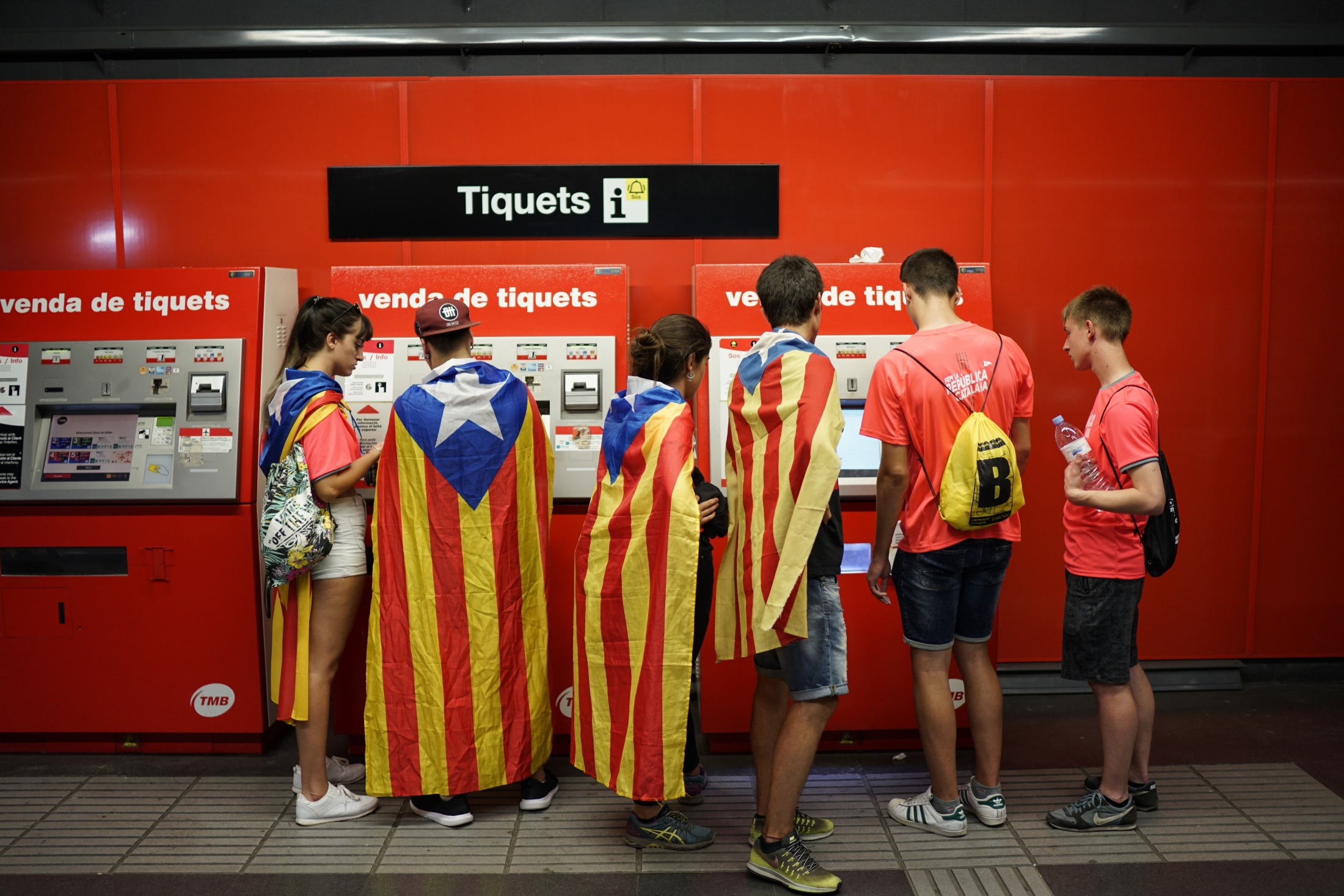 "(AP Photo/Daniel Cole) Youth carrying Catalan pro-independence flags on their shoulders get tickets for the subway on their way to a demonstration marking the Catalan National Day in Barcelona, Spain, Tuesday, Sept. 11, 2018. Catalan authorities have made a call to flood the streets of Barcelona later on Tuesday. Sept. 11, called ""Diada,"" marks the fall of the Catalan capital to Spanish forces in 1714."