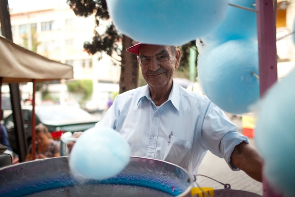 A cotton candy vendor poses for a portrait in Mexico City, Mexico. Photographed for Airbnb.