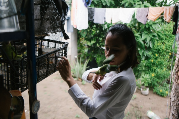 Iris Tobar Rodríguez plays with her pet parrot at her home in Jutiapa, El Salvador. Tobar Rodriguez plans on migrating to the U.S because of rising violence even after already being deported once.