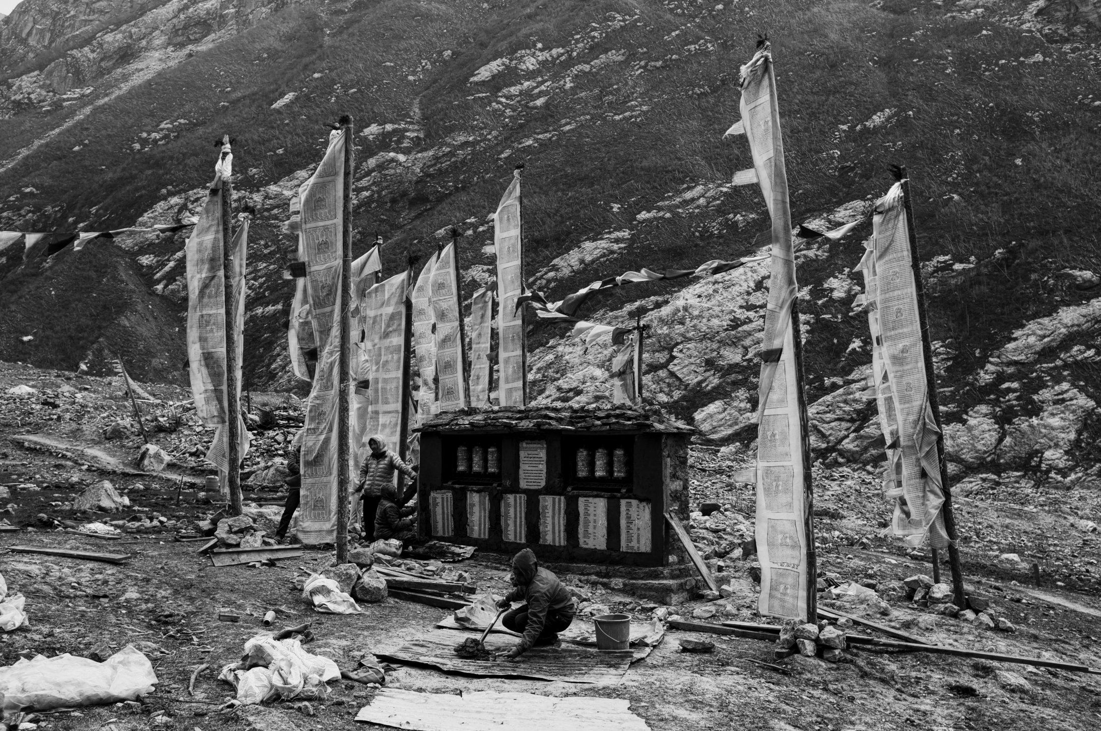 Local men finishing the construction of the memorial, surrounded by buddhist prayer flags.