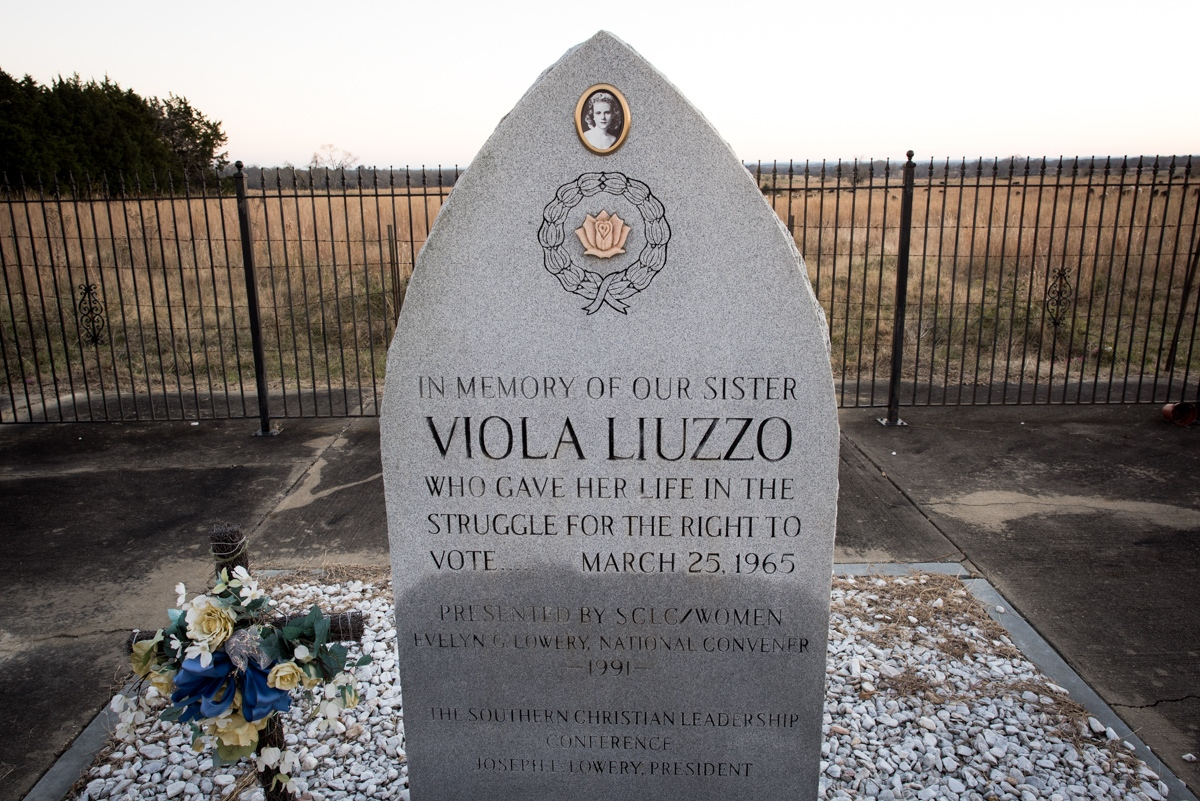 Lowndesboro, AL. 12/7/2015. On March 25, 1965, Viola Liuzzo and Leroy Moton, a 19-year-old local black activist, headed to Montgomery, Alabama to pick up the last group of demonstrators waiting to return to Selma. At 7:37pm, while stopped at a traffic light in front of the Edmund Pettus Bridge in Selma, they were spotted by four Klansmen, who were, according to the testimony from one of the Klansmen, had spent the day seeking an opportunity to kill Martin Luther King. When they saw Liuzzo, who was white, driving a car with Michigan plates after dark with a black man in her passenger seat, they decided to attack them instead. The Klansmen hoped that this would send a clear message about white supremacy to northern whites, southern blacks, and like-minded liberals. Engaging Liuzzo in a high-speed chase on Highway 80, they pulled alongside her car about 20 miles outside of Selma and fired. Liuzzo was killed instantly and Moton, covered in her blood, escaped by pretending to be dead. The discoloration on the lower portion of the memorial marker is the result of repeated vandalism – one time in particular, a large Confederate flag was painted across the face of the stone in 1997.