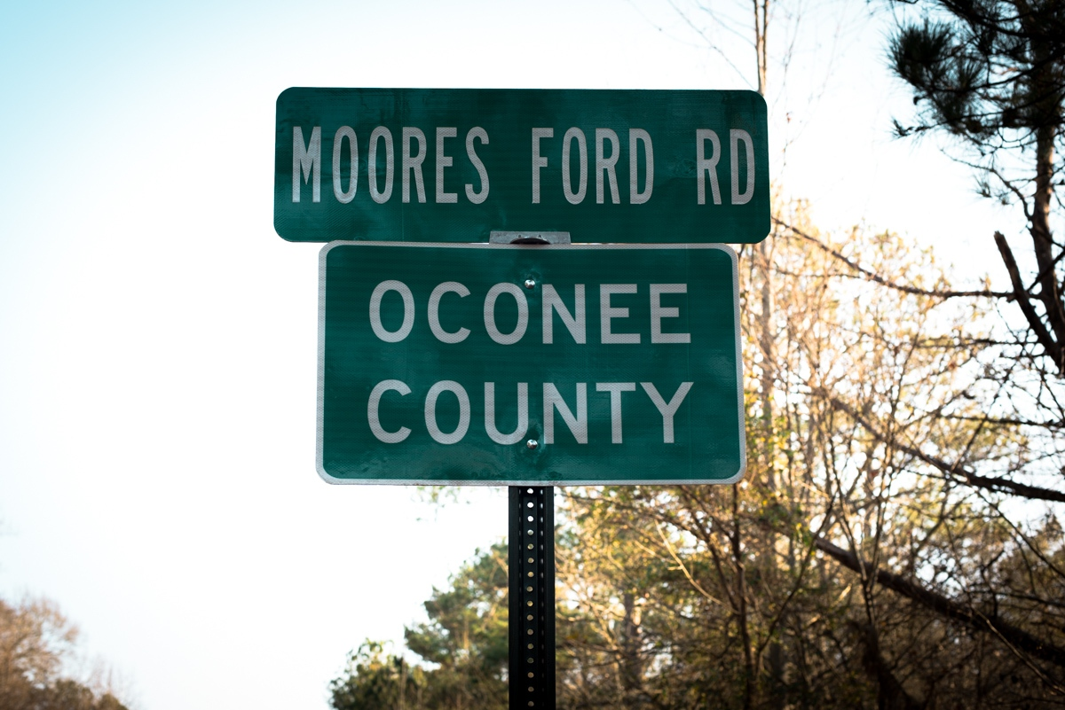 """Monroe, GA. 12/10/2015. The Moore's Ford Bridge incident, widely described as the US's last mass lynching, stands out as a particularly brutal case even in Georgia, where more lynching's were recorded between 1877 and 1950 than in any other state, according to an EIJ (Equal Justice Initiative) report. The victims of the lynching, who were African-American sharecroppers, were killed after Roger Malcom was bailed from Walton County Jail on charges of stabbing Barnette Hester, a 29-year-old white farmer. Hester was rumored locally to be having an affair with Roger's wife, Dorothy. The couples were seized by a crowd at Moore's Ford Bridge while being driven home in a truck by Loy Harrison, a white farmer who had paid to bail Malcom out of jail on July 25, 1946. The women were tied to an oak tree beside their husbands and the mob fired three times at point blank range hitting their victims 60 times. The crowd then cut open the stomach of Dorothy Malcom, who was 7-months pregnant and removed the fetus. Harrison, who escaped unharmed and said he was ambushed, has been accused by civil rights activists of being a Klan member and helping to set up the lynching. According to one witness, """"a Confederate flag was flown at the crime scene next to a Walton County Sheriff's car. This was to show people that this was a Ku Klux Klan killing and law enforcement was involved."""" For years, no one in Walton County would talk with authorities about the case. When a 1946 grand jury failed to identify any suspects, the FBI pulled out of the active investigation. In 2013, during an interview with the NAACP, Wayne Watson named seven men who he claimed to have heard speaking about their involvement in the murders. Watson alleged that all seven men, including his uncle were members of the Ku Klux Klan. The 69-year old case was reopened and is pending investigation by the FBI."""