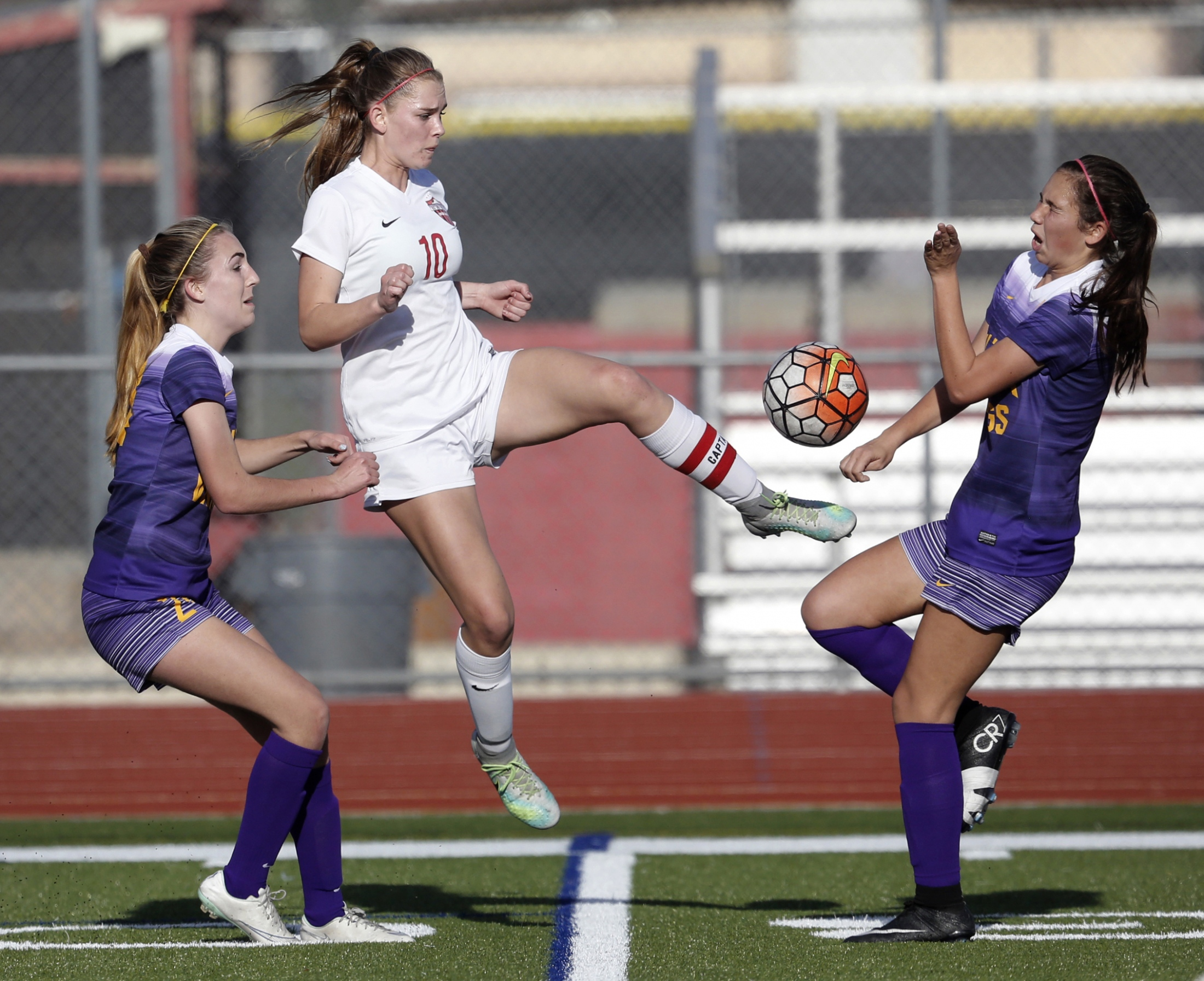 Hart's Taylor Scott (10) jumps to kick the ball away from Valencia's Kimberly Anderson (24), left, as Valencia's Kiana Kukaua (5) tries to avoid the ball during a soccer game at Hart on Thursday, Feb. 9, 2017. Katharine Lotze/Signal