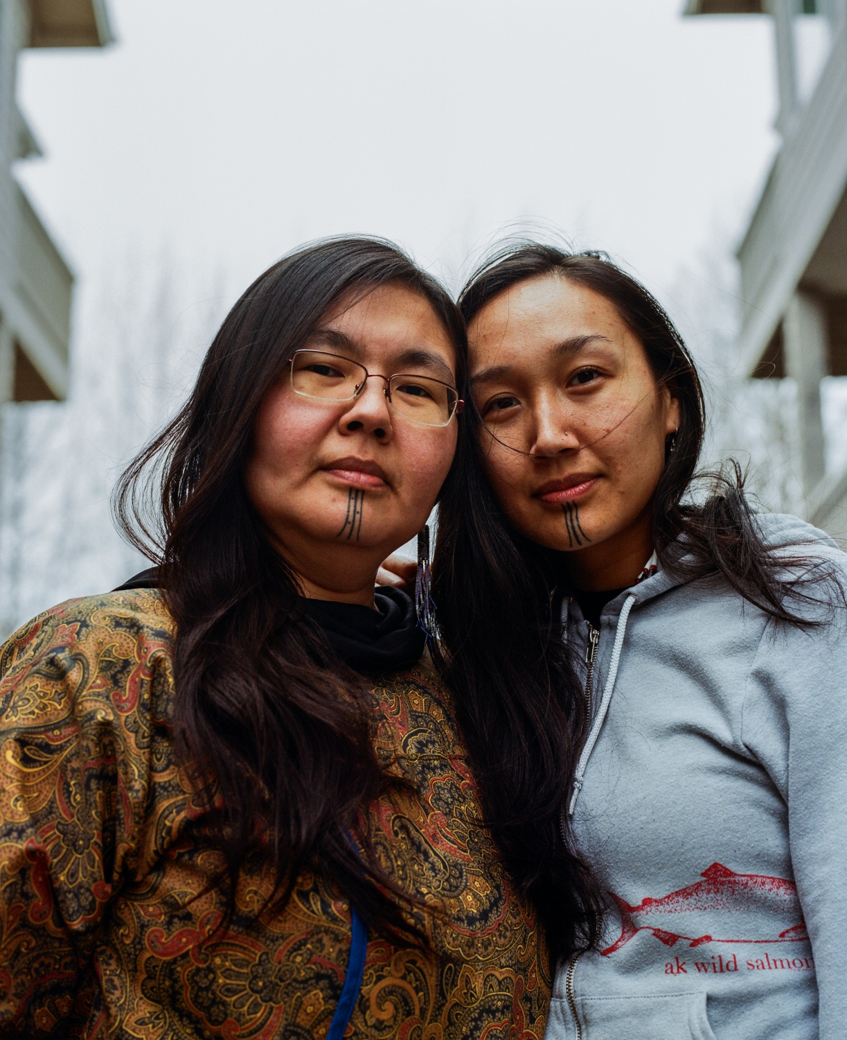 "Mellisa Johnson Heflin, who goes by her Inupiaq name Maktuayaq, 39, and Charlene Aqpik Apok, who goes by her Inupiaq name, Aqpik, 33, outside of Apok's home in Anchorage. The two women were in a master's program together, and say that they would stay up late talking to one another, and on one night, the conversation of traditional tattoos came up.  ""She was like ""for reals? You want one too?"" Apok says. ""And so then we planned on it from there.""  The two women went to get their tattoos together at a tattoo parlor, before women like Nordlum and Whalen-Lunn were reguarly doing the hand poke method in town. Both women teach Inupiaq in addition to holding positions at demanding full-time jobs (Heflin is the Executive Director at and Bering Sea Elders Group and Apok is a Researcher at Southcentral Foundation), and for each there is a strong connection to getting the tavlagun and to speaking their indigenous language.  ""There's so much to it,"" Apok says. ""With our creation stories, ceremony, rites of passage, gendered ceremonies, the sisterhood—the sisterhood of this—has been almost indescribable. Our language journey together. The placement of this by my mouth—that is something I would speak to as well in saying that our words are so powerful, and what comes out of our mouths is so powerful—it was a reminder for me to speak my truth, and to not be afraid to speak my truth, and that it's valid. And also to be mindful to not say anything I would want to take back. It holds you highly accountable for what you speak into existence."""