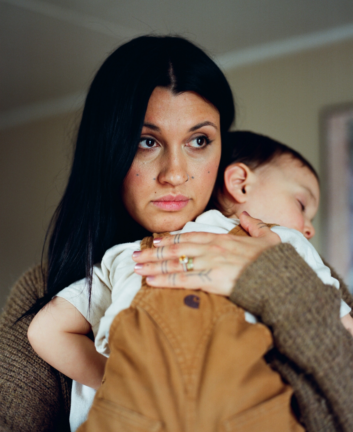 "Keegan Richards holds her daughter, Estelle, 2, in her home in Anchorage, Alaska. Richards is a stay-at-home mom who also designs traditionally-inspired modern atikluks for her business Tundra Mama. Richards, Nordlum's cousin, has had multiple tattoos done by Nordlum, including the Sassuma Ahrna lines on her hands, dots on her cheeks, and most recently, chin lines. When she decided to do the dots on her cheeks even though they are not traditional to Inupiaq culture, she said a lot of it came down to understanding that the tradition itself is now something that's changed because it is a revitalization. ""We now live in a Western world and things have evolved and changed, and while it is a traditional tattoo that is done in a traditional way, I feel that it is modern because I was able to look across the board and pick something that resonated for me and what I identify with and then come up with my own meaning for it. Because [the tattoos] all had different meanings and different families got different designs for different reasons. They all had their own story behind them. And because two generations of women in my family do not have these markings, I feel like we are at a place where you can start that tradition over again. And I can get these dots to represent 10 women in my life that have had an impact on me, past or present, that will continue to impact my journey. And maybe one day, my daughter will have a tribe of her own of amazing women and want to honor them in some way, and maybe it will look like this and maybe it won't, but it opens the door for her to be able to do that."""