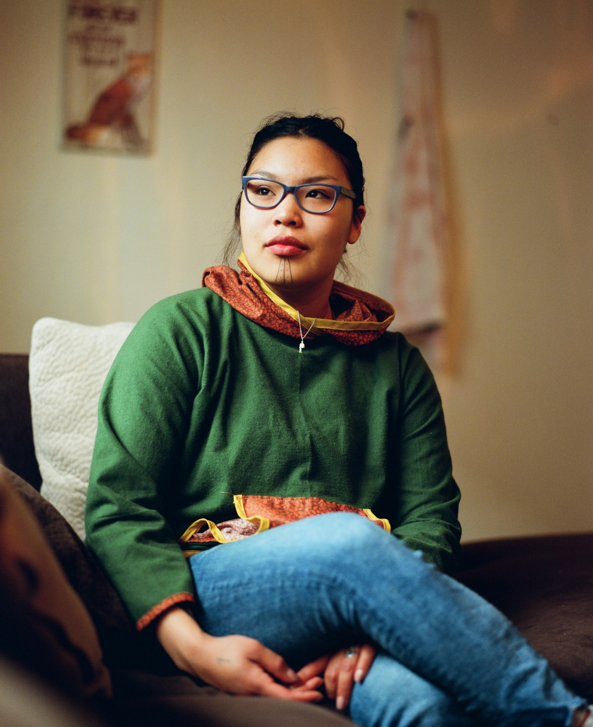"Danyal Harvey, 20, in her home in Anchorage, Alaska. Harvey was tattooed by Sarah Whalen-Lunn when she was 19 in Feburary 2018. She says that getting her tattoo was a decision that she spent a lot of time thinking about, but that once she did it, she felt like a more complete person. Her Inupiaq language instructors had the chin tattoos, and she says that when she first saw them, she thought, ""these women are so beautiful and strong in their culture and they make me want to be better and learn more about my culture.""  Harvey grew up in the village of Noorvik until she was 7, but then spent life between Fairbanks and boarding school in Galena before coming to Anchorage. When she would return to the village for summers, she says that she often felt out of place.  ""When I went back to Noorvik, people said that I sounded like a white girl,"" she says. ""I was like, 'I literally have no choice about that. I grew up basically in the city. I didn't have a chance to be in the village like the rest of you.' So, I feel like my tavlugun is saying like, 'hey, I'm Inupiaq, too. I'm from here. I'm still one of you'.""  One of her other reasons, she says, had to do with getting out of an unhealthy relationship. ""When I got my tavlugun, that was a part of it, too. Saying, 'I deserve more. My people have been through so many hardships for me not to be free.' It is a daily reminder that I'm worth all of the love that the world can give me. And that my people, and my ancestors, have been through too much for me to feel captured and to be being abused. That's not for me at all. And it's a daily reminder.""  There have been some criticisms to her tattoo, she says, but not many. When she first posted about her chin tattoo on Instagram, a friend messaged her and told her that she shouldn't have gotten it, that she wasn't appropriately heeding tradition. ""At this point, culture evolves,"" Harvey says. ""This tavlagun to me means something different than what other ladies' tavlaguns mean to them. I feel like people need to know that. That you do need to account for tradition. But when you're trying to bring something back, it evolves."""