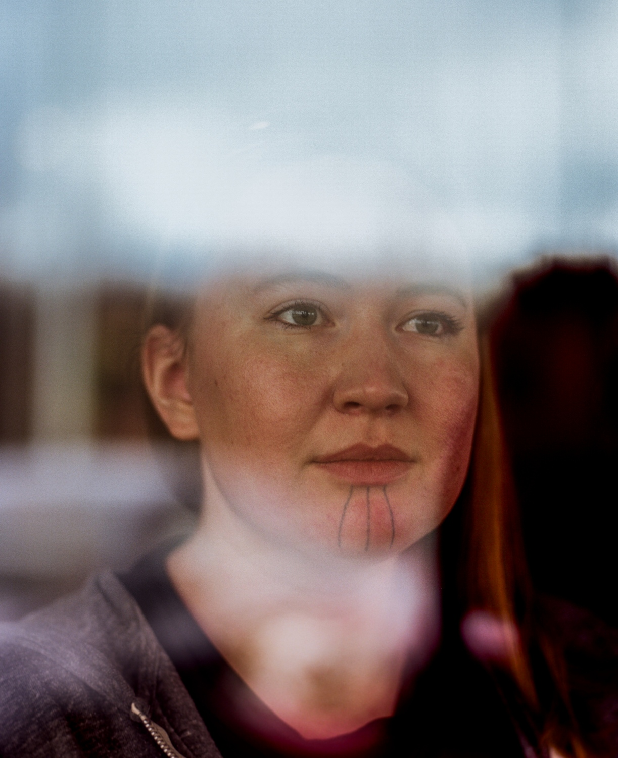"Stacey Lucason, 28, at Kaladi Brothers Coffee in Anchorage, Alaska, the place where, for the first time in her life, a stranger approached her and spoke to her in Yup'ik after she had her chin tattooed. Because she is an eigth Yup'ik, she says, she usually passed as non-Native, which often made her feel invisible.  ""Because I could pass, people used to feel very comfortable saying negative things about Natives,"" she says. ""Since I've had it done, at least here [in Alaska] that happens way less often. Or people will be like, 'So, not you, but,' and so they'll sort of recognize that they're not in the space they thought they were or that there is somebody from the Yup'ik people or from a Native group in the room. It reminds them, I hope, that maybe if you're pausing to say that, then maybe you just shouldn't say it.""  Lucason decided to have her chin tattooed right before graduating from the University of Alaska, a marker in life that felt like a modern-day coming of age to her. She had worn the lines on her chin in eyeliner for months before getting the permanent tattoo, and then was the first woman to have her chin tattooed by Holly Nordlum."