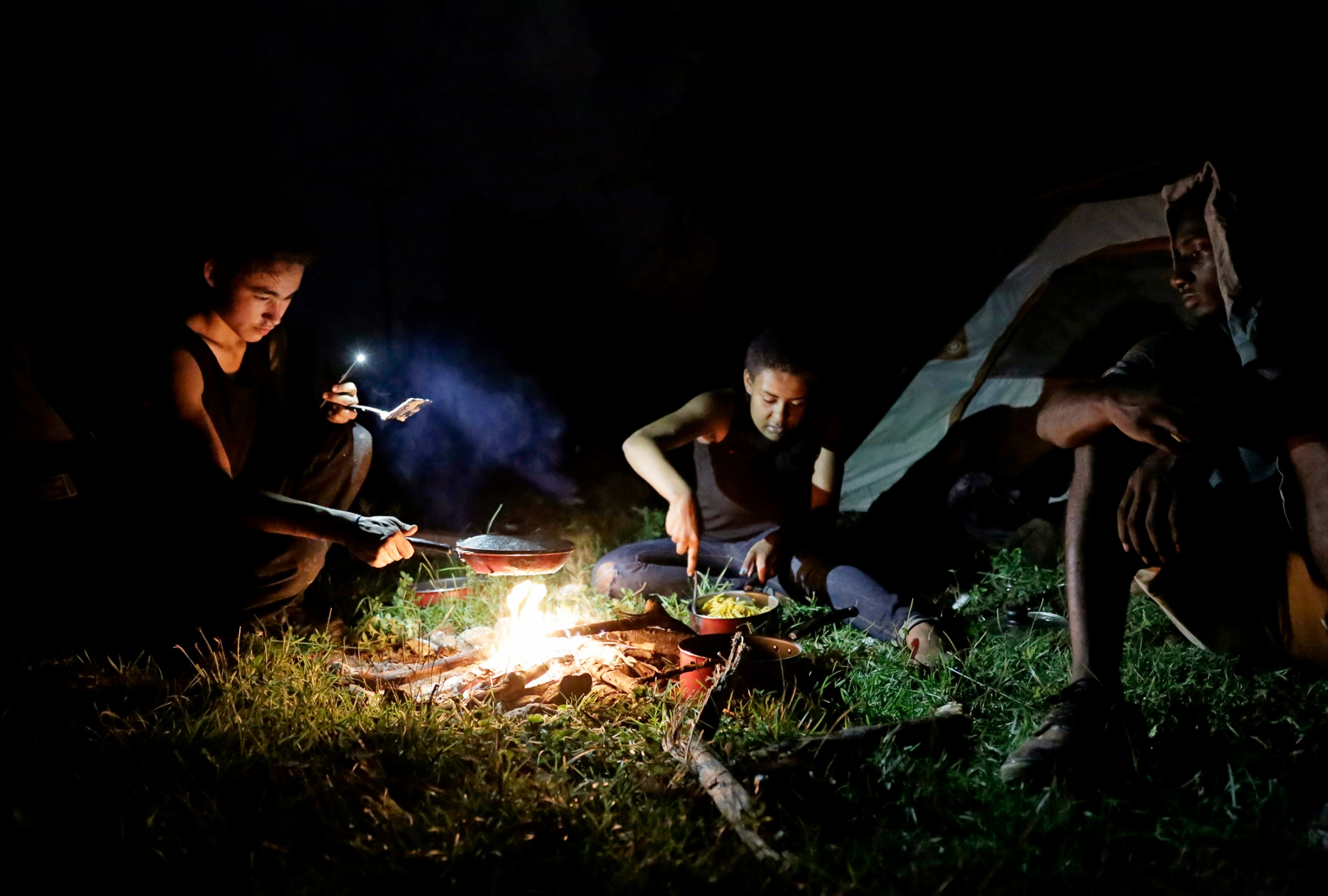 From left: Robert Bulens, Ravyn Frazier and Andy Hall make a dinner of noodles with cream of mushroom soup at their campsite in a clearing hidden off the side of a highway in Tallahassee, Fla, on Sept. 20, 2018.   Hot and saturated with mosquitoes and fire ants, they stay just long enough to set up camp, cook and wash dishes in the stream on the other side of the railroad tracks before heading back into town with plans to return to the campsite to sleep. Usually the group stays the night under shelter with whichever friend happens to have an apartment at the moment. Sleeping at the campsite is a last resort when other plans fall through. Bulens keeps the site a secret so he can moderate who stays there, making sure they are trustworthy.  No strange roommates, no rules, and no evictions. Having attended a culinary program in junior college, Frazier wanted to be in charge of dinner, making sure the others knew she would cook the fettucine al dente so it wouldn't be mushy.
