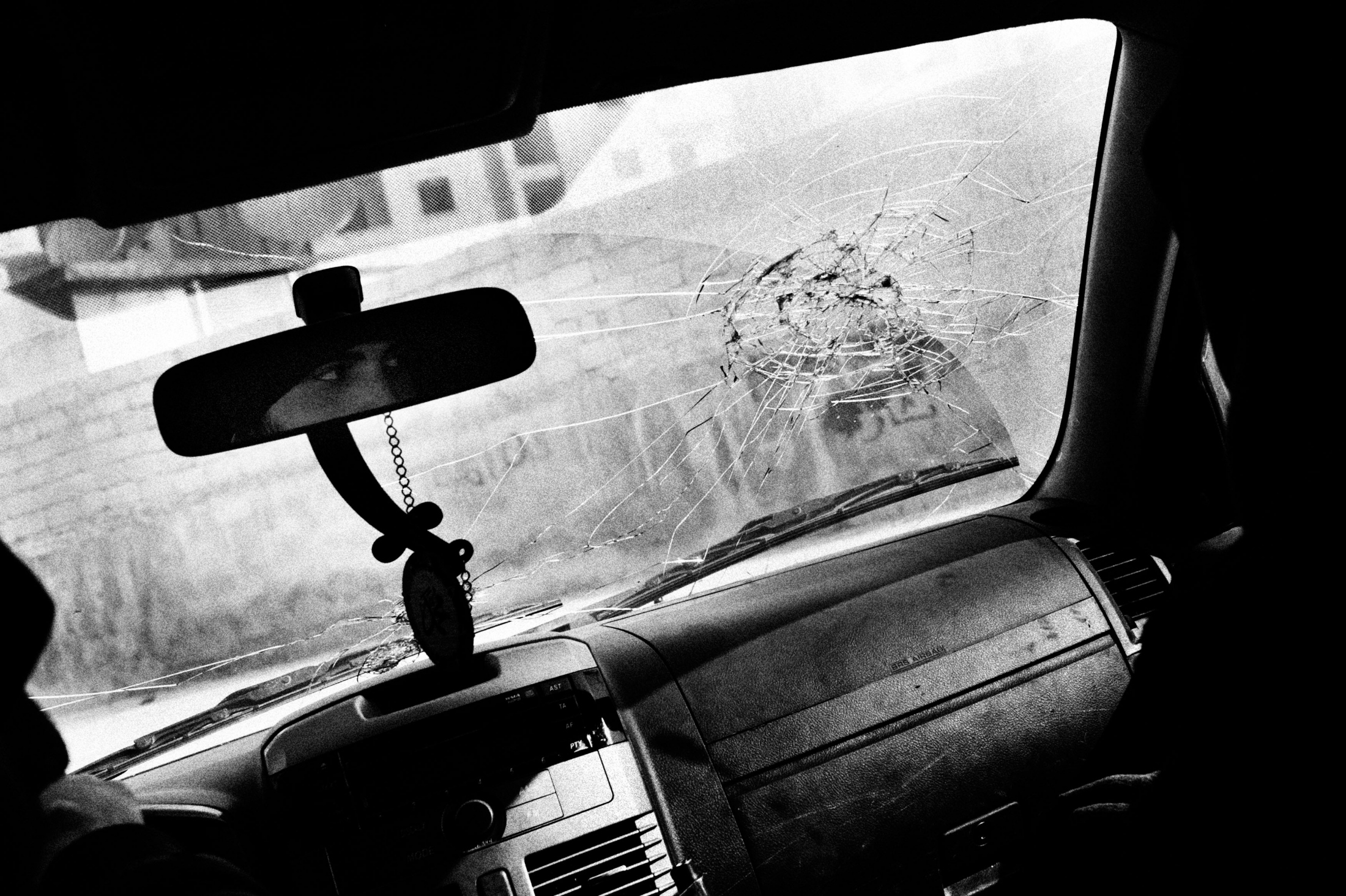 "The eyes of a man are seen through the mirror inside a car that was heavily shooted the day after the picture was taken in the neighborhood of Izaah in Aleppo, Syria, Wednesday, Jan. 3, 2013. The United Nations estimated that more than 400,000 people have been killed in Syria's 60-month-old uprising against authoritarian rule, a toll one-third higher than what anti-regime activists had counted. The U.N. human rights chief called the toll ""truly shocking."" Copyright: Spanish Photojournalist Andoni Lubaki"