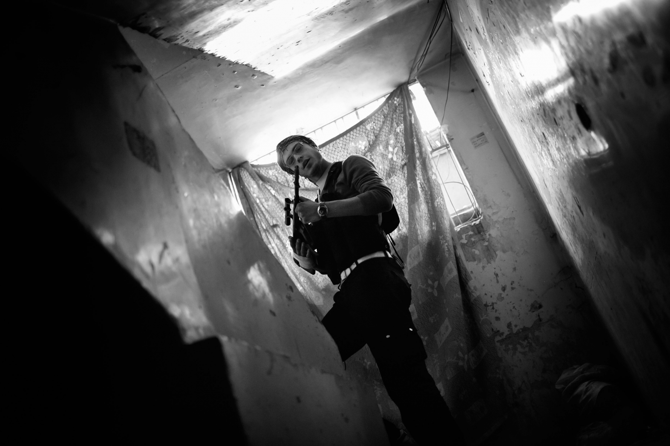 """A Syrian islamist rebel called Jamil shows his weapon inside a abandoned building in the Izaah neighborhood of Aleppo, Syria, Wednesday, Jan. 3, 2013. This pictures was the last one of Jamil before he was shoot dead some hours after. The United Nations estimated that more than 400,000 people have been killed in Syria's 60-month-old uprising against authoritarian rule, a toll one-third higher than what anti-regime activists had counted. The U.N. human rights chief called the toll """"truly shocking."""" Copyright: Spanish Photojournalist Andoni Lubaki"""