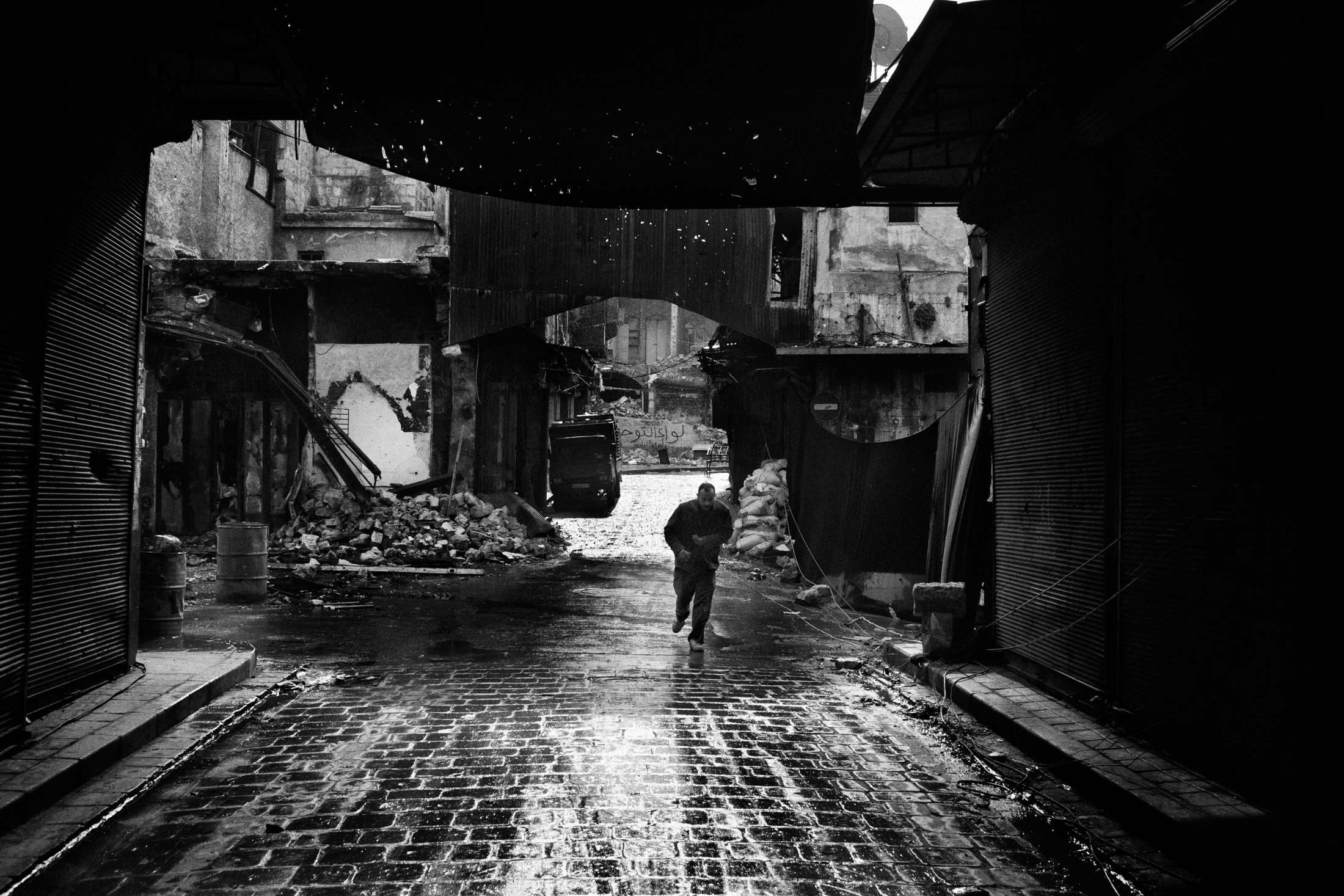 """A man running across the street blinded by blankets (right part of the image) to avoid the shoot of a snipper loyal to Assad in the Old City of Aleppo, Syria, Wednesday, Jan. 6, 2013. The United Nations estimated that more than 400,000 people have been killed in Syria's 60-month-old uprising against authoritarian rule, a toll one-third higher than what anti-regime activists had counted. The U.N. human rights chief called the toll """"truly shocking."""" Copyright: Spanish Photojournalist Andoni Lubaki"""