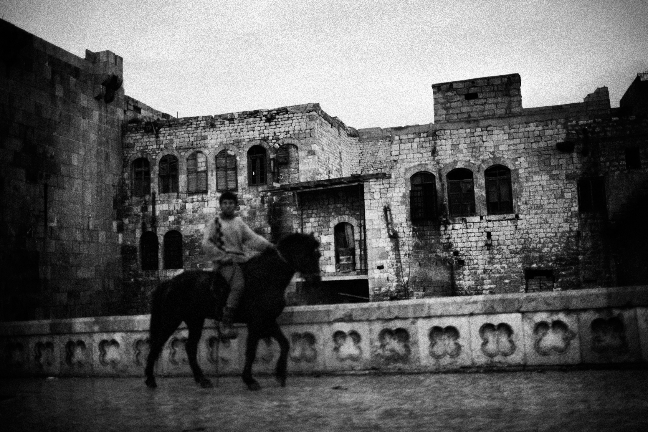 """A boy riding a horse near the Old Town frontline of Aleppo, Syria, Wednesday, Jan. 6, 2013. The United Nations estimated that more than 400,000 people have been killed in Syria's 60-month-old uprising against authoritarian rule, a toll one-third higher than what anti-regime activists had counted. The U.N. human rights chief called the toll """"truly shocking."""" Copyright: Spanish Photojournalist Andoni Lubaki"""