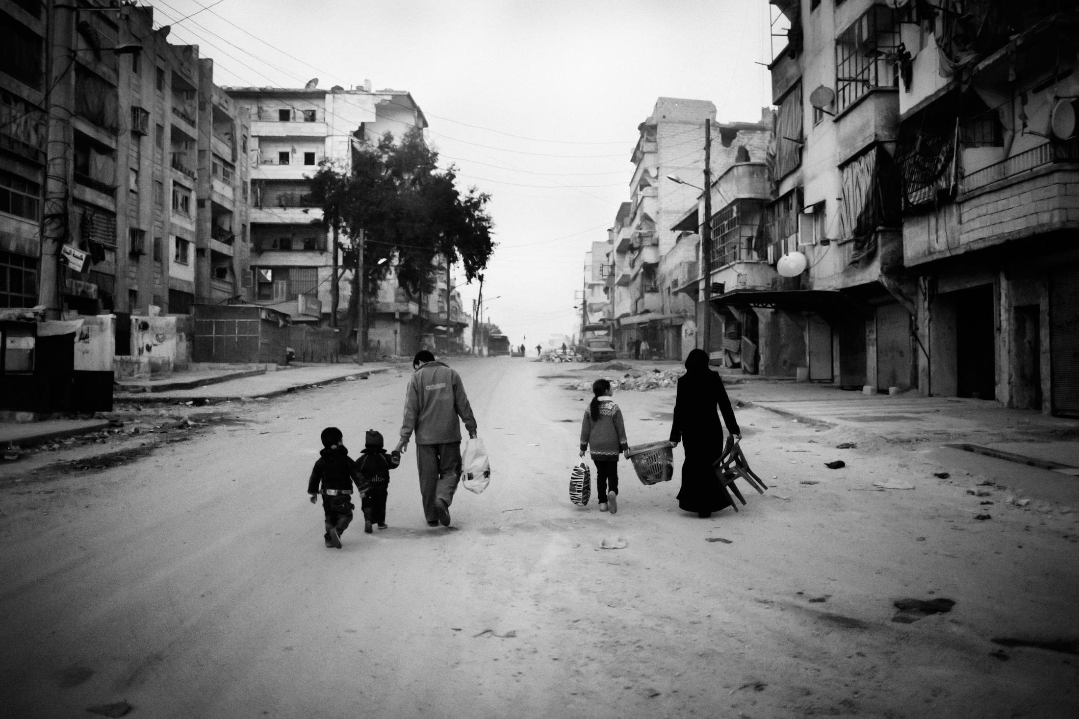 """A family walking through the streets in the Al-Amriyah neighborhood of Aleppo after take the last belongings that they rescue from their destroyed house, Syria, Wednesday, Jan. 2, 2013. The United Nations estimated that more than 400,000 people have been killed in Syria's 60-month-old uprising against authoritarian rule, a toll one-third higher than what anti-regime activists had counted. The U.N. human rights chief called the toll """"truly shocking."""" Copyright: Spanish Photojournalist Andoni Lubaki"""
