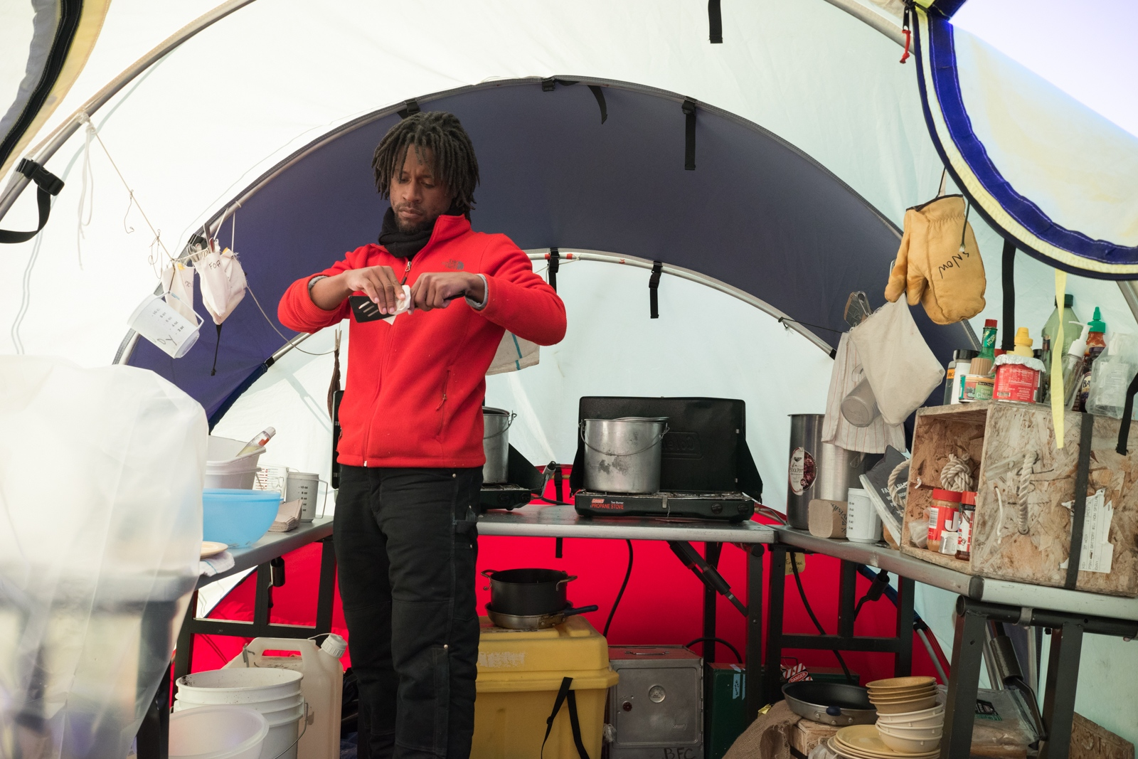 Dr. Brian Atkinson preparing food in the kitchen tent at Graphite peak. The team was stuck here for an extra week while a storm raged between them and the main Shackleton camp. 26 December 2017.