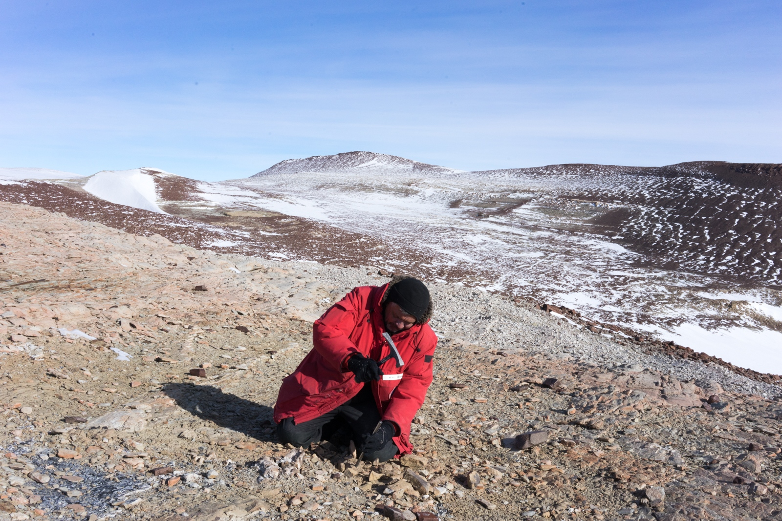 Unearthing plant leaf fossils, Dr. Serbet uses his hammer and pick to get into a deeper layer of rock. In a place known as Alfies Elbow, at over 10,000 feet, the wind rips hard down from the Antarctic plateau. 14 December 2017.