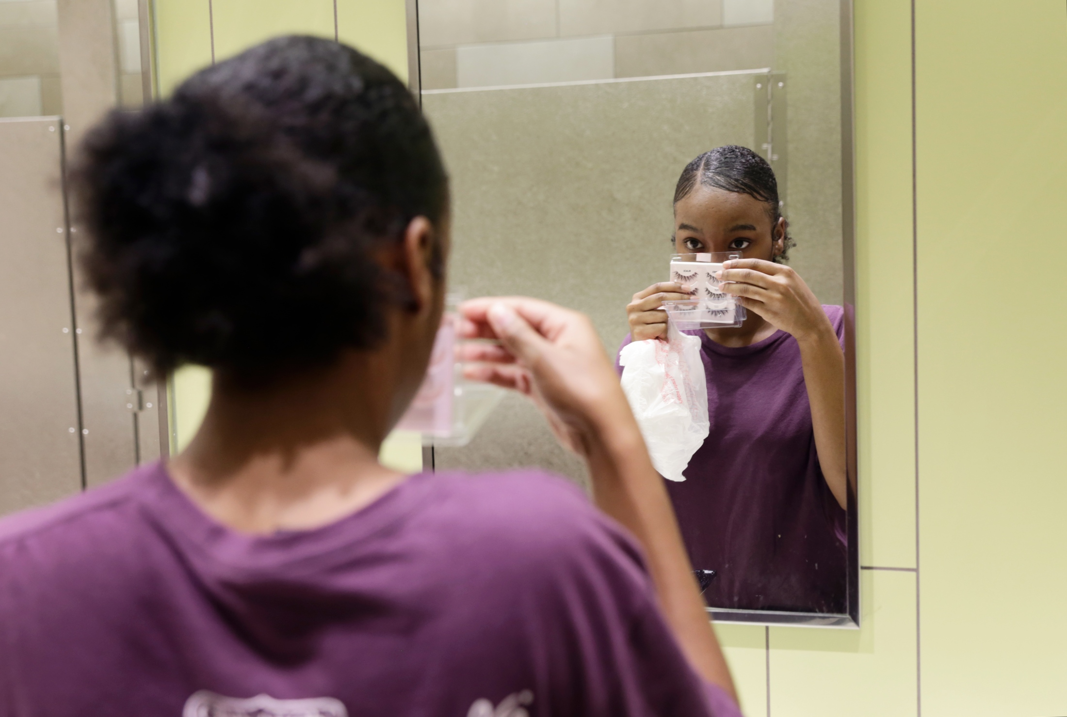 Samiah Williams, of Tallahasseee, Fla., prepares to put on her new eyelashes in the Governor's Square mall bathroom on Aug. 18, 2018, before her shift at Cinnabon. After couch surfing for a year, having been kicked out of her sister's house, Williams has made great strides against the odds, acquiring a job, moving into a transitional living home and enrolling in high school with the help of her Capital City Youth Services street outreach program caseworker.