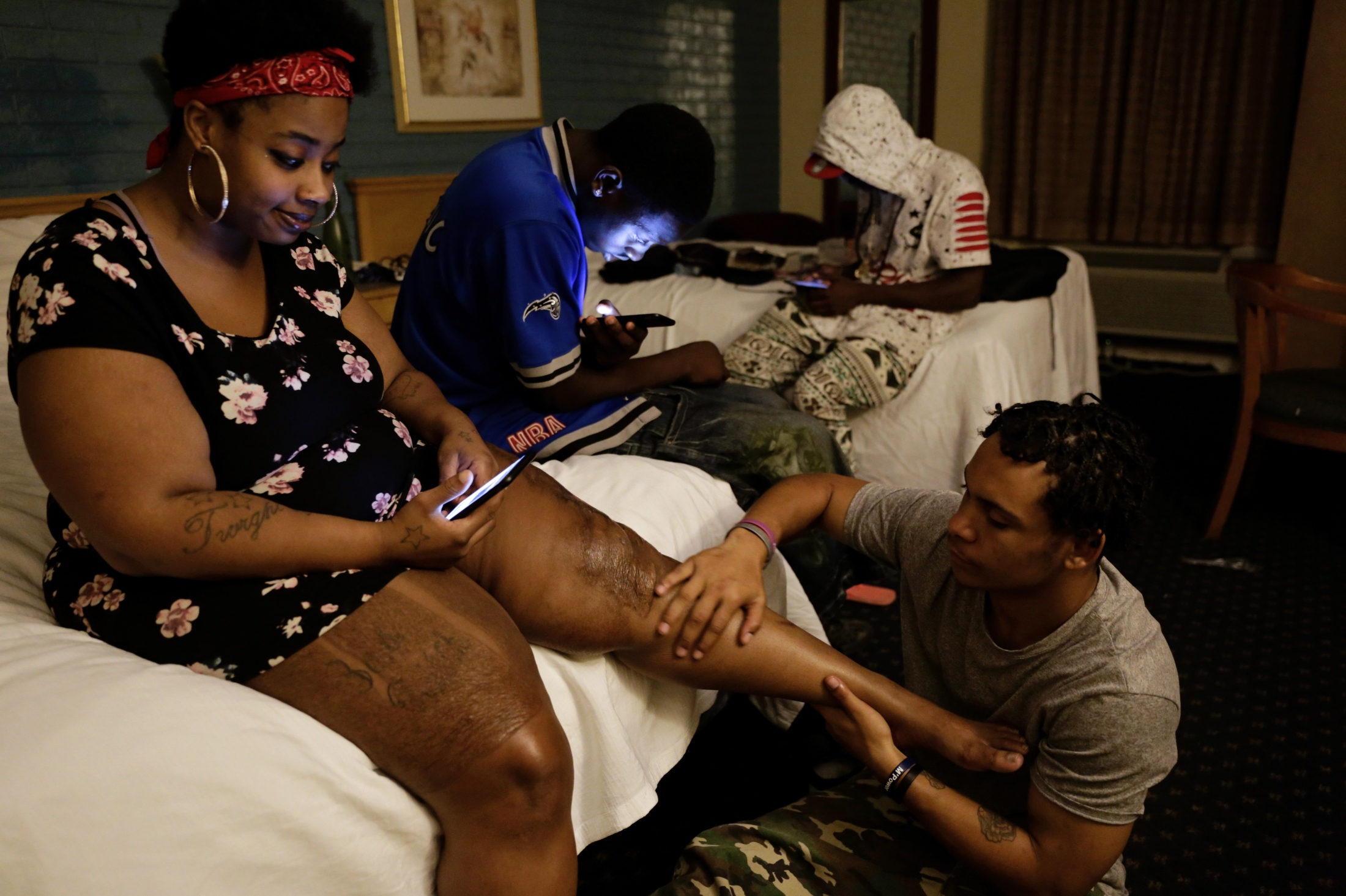 Redd, who only goes by her first name (far left) gets a vaseline rub-down by Mike McLaughlin at the LaCasa Motel in Tallahassee, Fla. on Aug. 14, 2018. Their friends Ladarius Simmons (center left) and Jammoris Mosely (center right) interact with their cell phones. Redd has been staying at the motel for about two weeks, paying for the room each night with sex work, before McLaughlin, Simmons and Moseley moved in. They manage to stay at the motel with more people in a room than is allowed by changing names on the rental agreement. This group of homeless youth in Tallahassee relies on social networks for shelter and emotional support.