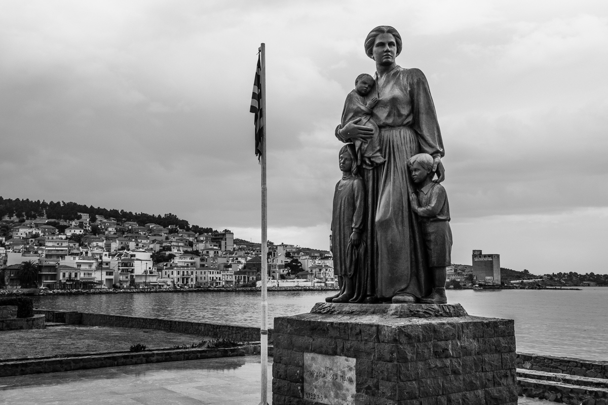 """div"""" data-cycle-speed=""""550"""" data-cycle-timeout=""""5000"""">Situated on the waterfront of Epano Skala, near the Old Harbor, the statue of the Asia Minor Mother was erected to honour hardship and bravery. The statue depicts a mother holding a baby, with a young girl and boy clutching her legs, all embracing in solidarity. They represent the women and children who came from Asia Minor (Turkey) to Lesvos in 1922, in order to start a new life after the Greek-Turkish War of 1919-1922. So weird."""