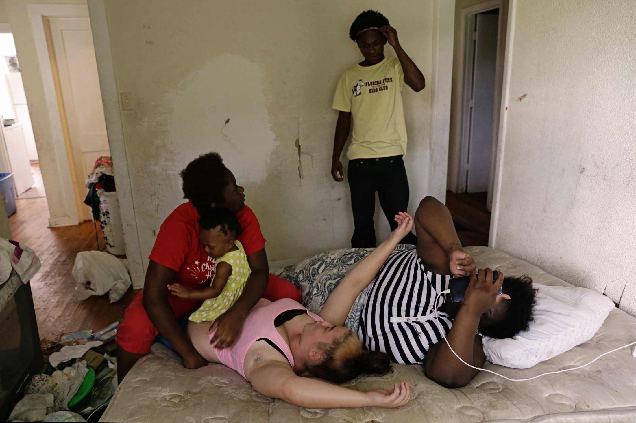 "Elizabeth McKinney, her daughter Arinna Ross, Jasmine Fields and Tylee Wooten hang out on the bed while talking to Tyrese Ross (standing). They live in a house that includes 14 youth and children in Tallahassee, Fla. The group of homeless youth ""double up"", squeezing as many cohorts into a space as possible. Social networks are of utmost importance for survival."