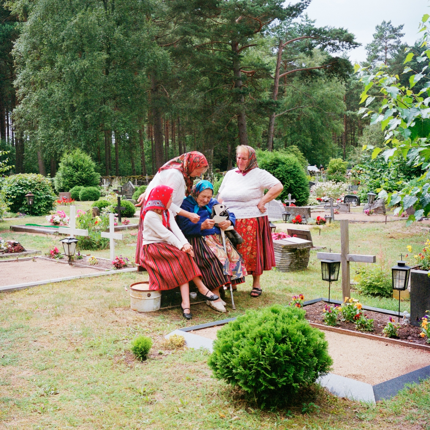 Women are visiting the ancestors at the cemetery after the mass. In Kihnu, the skirt is full of meaning. When grieving they are black, then blue is introduced to finally return to a bright red. Unlike the skirt, the color of the head scarf does not hold any special meaning. July 2014.