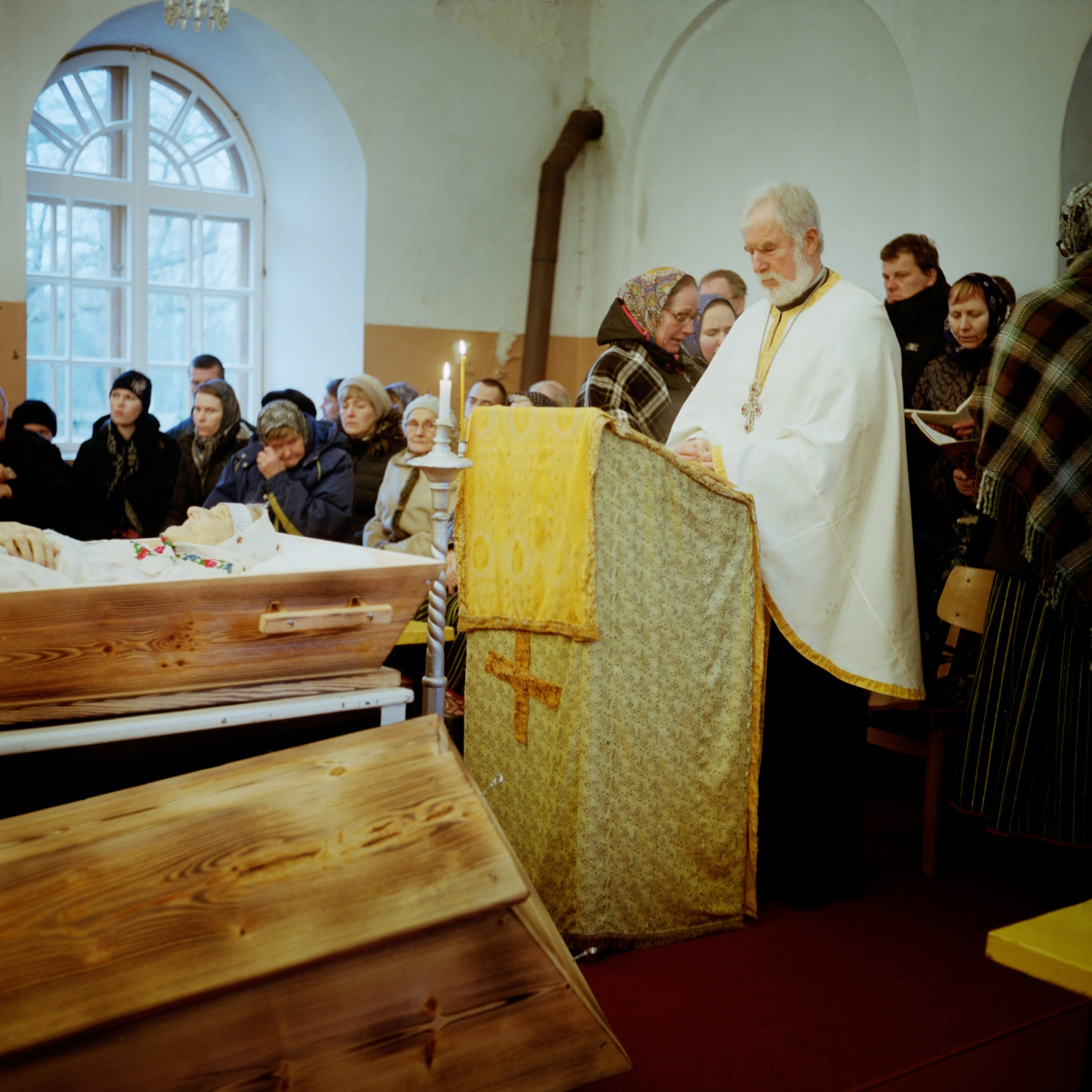 Kandi's funeral led by father Viktor Merik. A women's choir sings during the last farewell at the religious ceremony. Father Merik is from the continent and come to officiate in Kihnu. December 2017.