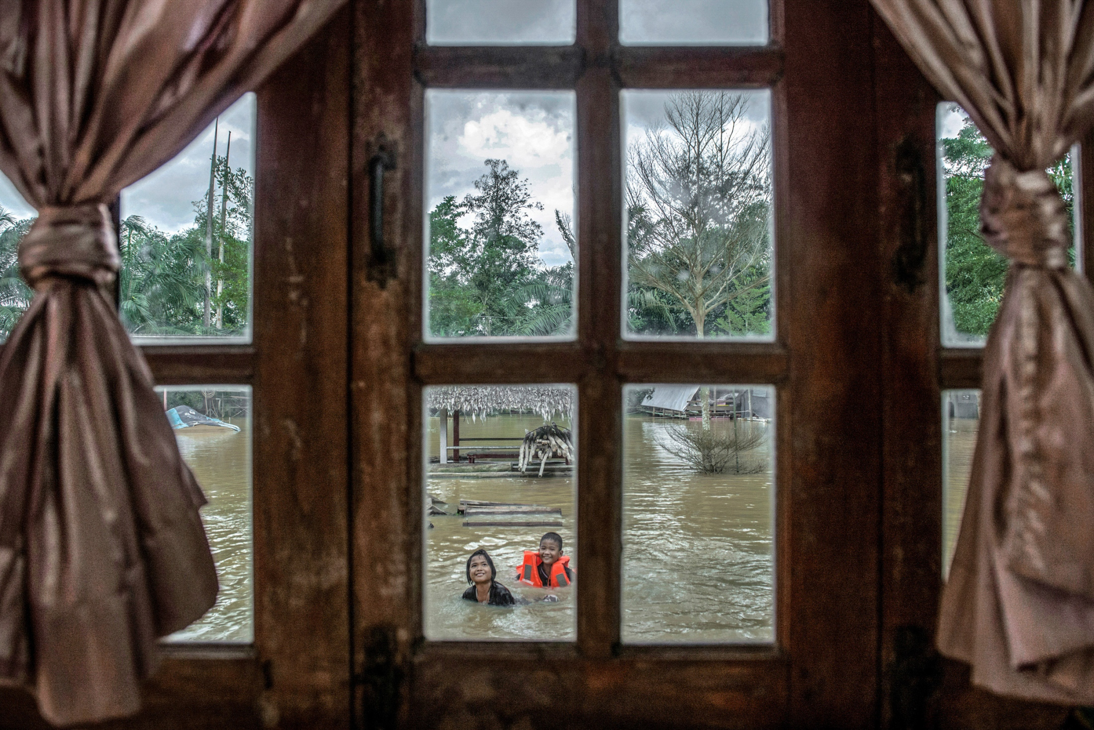 Many homes have been flooded for many weeks from the unseasonably heavy rainfall in Southern Thailand. The backyard has turned into a large flooded swamp. Surat Thani, Thailand- January 18, 2017.