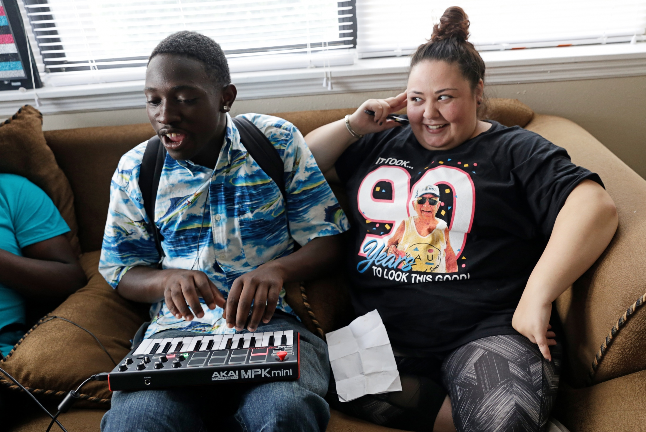 Ladarius Simmons, goofs around on a keyboard while Going Places caseworker Bri Tebbens watches.