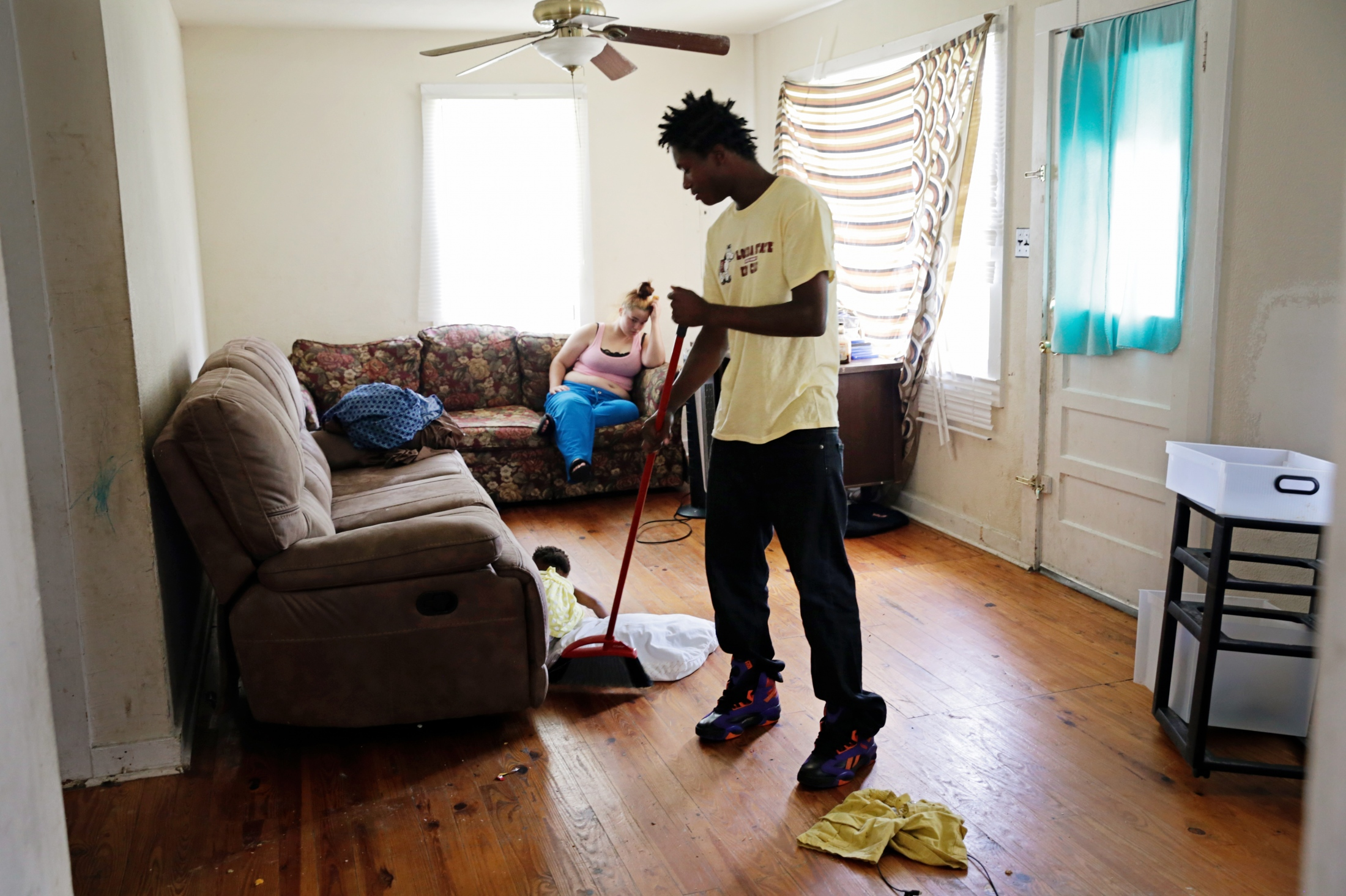 Tyrese Ross sweeps up the living room of the place he's sleeping, for now, that he shares with 13 other people.