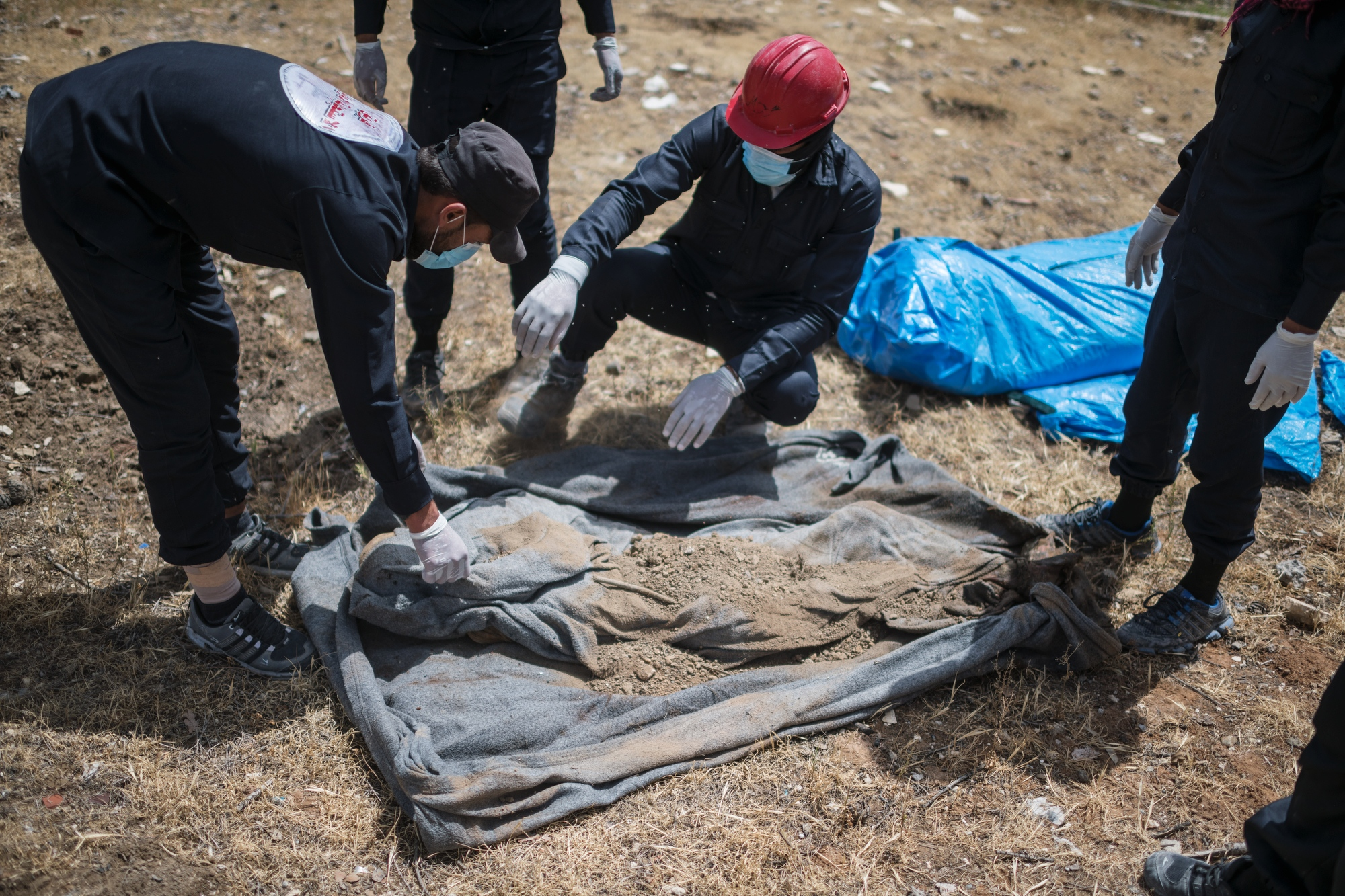"The first responders team in Raqqa uncovers the remains of a woman after searching for bodies and human remains in Hediqat Al-beida, ""the white park"", in Raqqa."