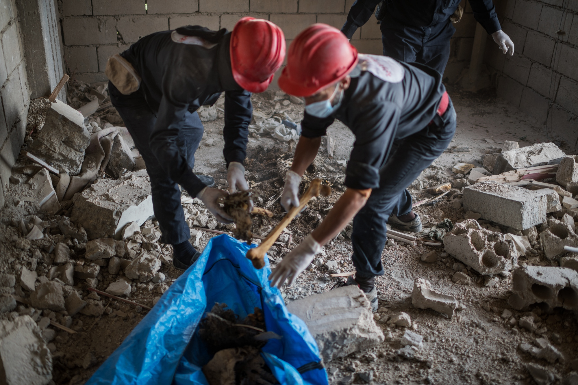 The first responders team have found two bodies on the second floor of a residential building. They are trying to check for improvised explosive devices and state that the bodies have remains of suicide vests on them. After seeing that nothing exploded they start scraping up the human remains and put them in a body bag.