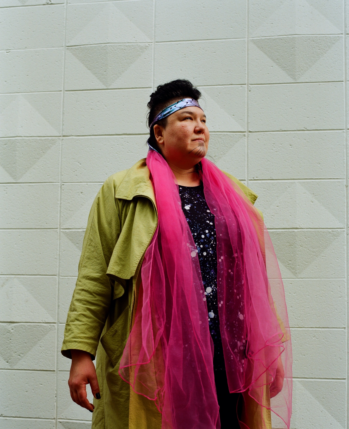"Allison Akootchook Warden, an Iñupiaq hip hop artist and performance artist also known as AKU-MATU, outside of her home in Anchorage, Alaska. Warden had her chin tattooed for the first time when she turned 40, and she chose a design done with color. ""I wanted to do color because I thought that if my great-grandmother had access to color, she would have chosen color,"" she says.  Warden had thought about having her chin tattooed for a while, she says, but decided to do it after her mother had hers done to mark turning 70.  ""My mom was marking that she was turning 70. And for her to get that done because she was a Presbyterian Minister sent a big signal I felt. Because she was trained in the church and she has a Masters Degree in Divinity, and she is a big leader in church. So for her to do that and show it so visibly, it was a big push for others I think—to say that it's not something that is conflicting with Christianity. That it's okay to have that part of our culture and it's not something to be ashamed of or to put away. I got mine done a year after that,"" she says. ""For me, it's a process of decolonization. We have the right to wear these tattoos. I feel like there's a strength in knowing who we are. There's intentional decolonization. Creating spaces to decolonize and decolonizing ourselves."""