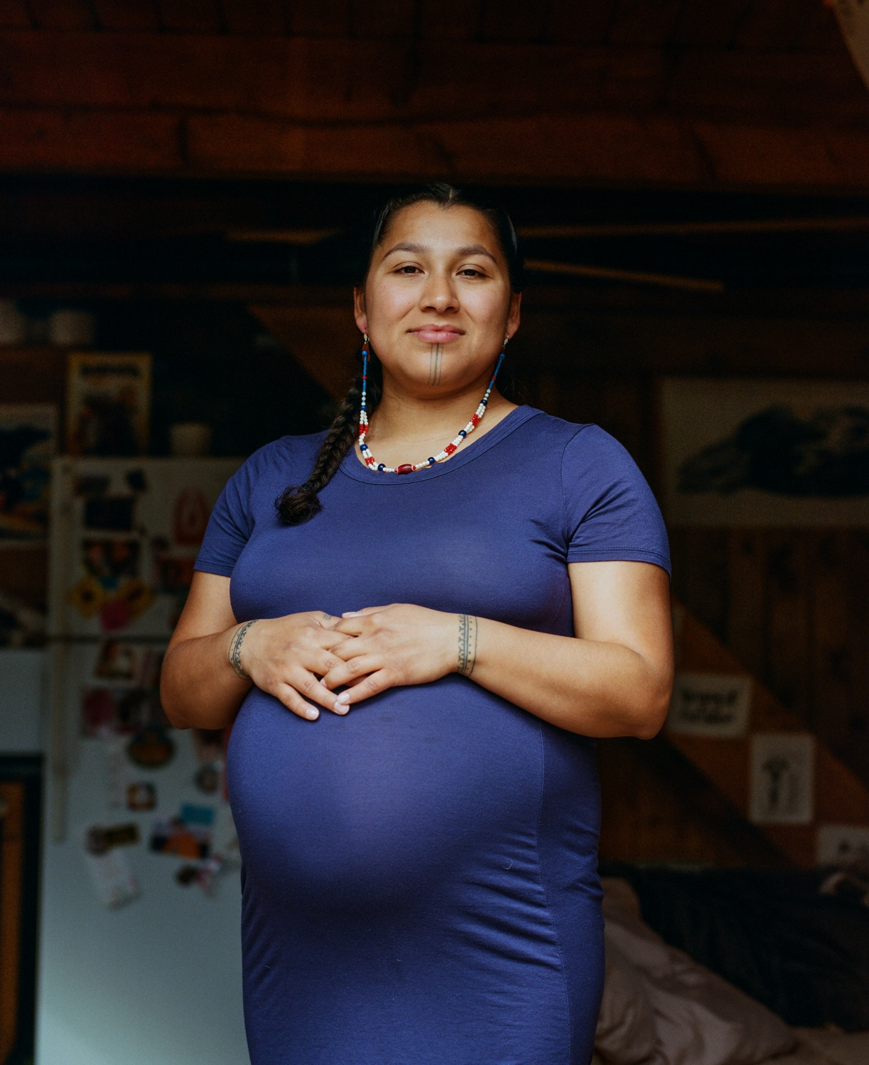 "Marjorie Tahbone inside her home in Fairbanks. Tahbone is a traditional tattooist who is currently working on her master's in Indigenous studies and writing her thesis on traditional tattooing and ceremony, with a personal lens on the tradition's connection to motherhood.  ""We as indigenous people have been through a lot in the last couple hundred years. I like to say that this was a tradition that went to sleep. It was something that was put away for a little bit during a rough time in our history, but it wasn't gone. It was there, on some level, whether it was through photography images or through stories, and it is being reawaken during this time of healing not just for the Inuit women who have been involved in it but for the entire community. And there have been people who have been unsure of this movement, maybe a little scared of how it will be interpreted by other people, non-indigenous people, because there still is this underlying oppression that's continually occurring within our communities from non-Native people and Native people—lateral oppression and lateral violence is a real thing that's happening right now and we are working through it. And we are healing from the historical trauma. And one of the ways that we are doing it is through the revitalization of our traditions and our languages. The tattooing is one that's taken a huge wave of awesome energy all across Inuit country. I've never seen anything quite like it as far as reviving our traditions because it really has taken the entire circumpolar north with Canada, Greenland, and Alaska coming together and working on this movement. Each of the reasons vary –they vary between each woman, they have their own personal stories that go with it, but the underlying foundational meaning is strength, is identity, it's about who we are as Inuit people and that we are still here today. We're still present, we're still going to be , we're not going anywhere and this is a tradition that's here to stay. It's something that's pretty powerful when you think about it,"" she says."
