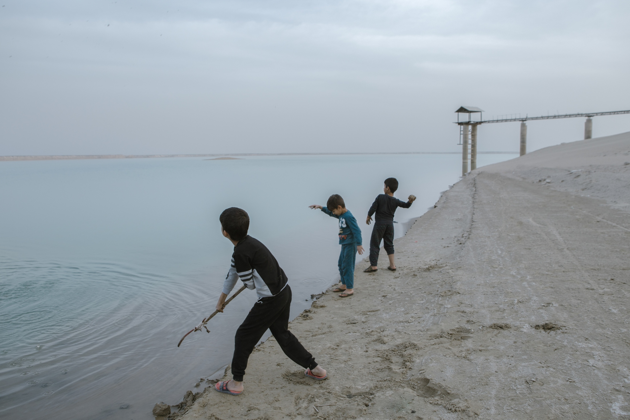 Children are playing around the Chah Nimeh reservoirs. The Chah Nimeh reservoirs are large natural holes in Sistan province into which Hirmand river water is directed. In times of water shortage, Sistan's drinking water and some part of its farming water are provided through this artificial lake. The only sign of water in the Sistan landscape is the Chah Nimeh reservoir. During 20 years, the Hamun wetlands had vanished after the South Asia region was hit by the most persistent drought. besides building many dams at the Upstream Hirmand, Afghanistan refuses to adapt to Iran's water rights and violates its water agreements.  Sistan province.2018