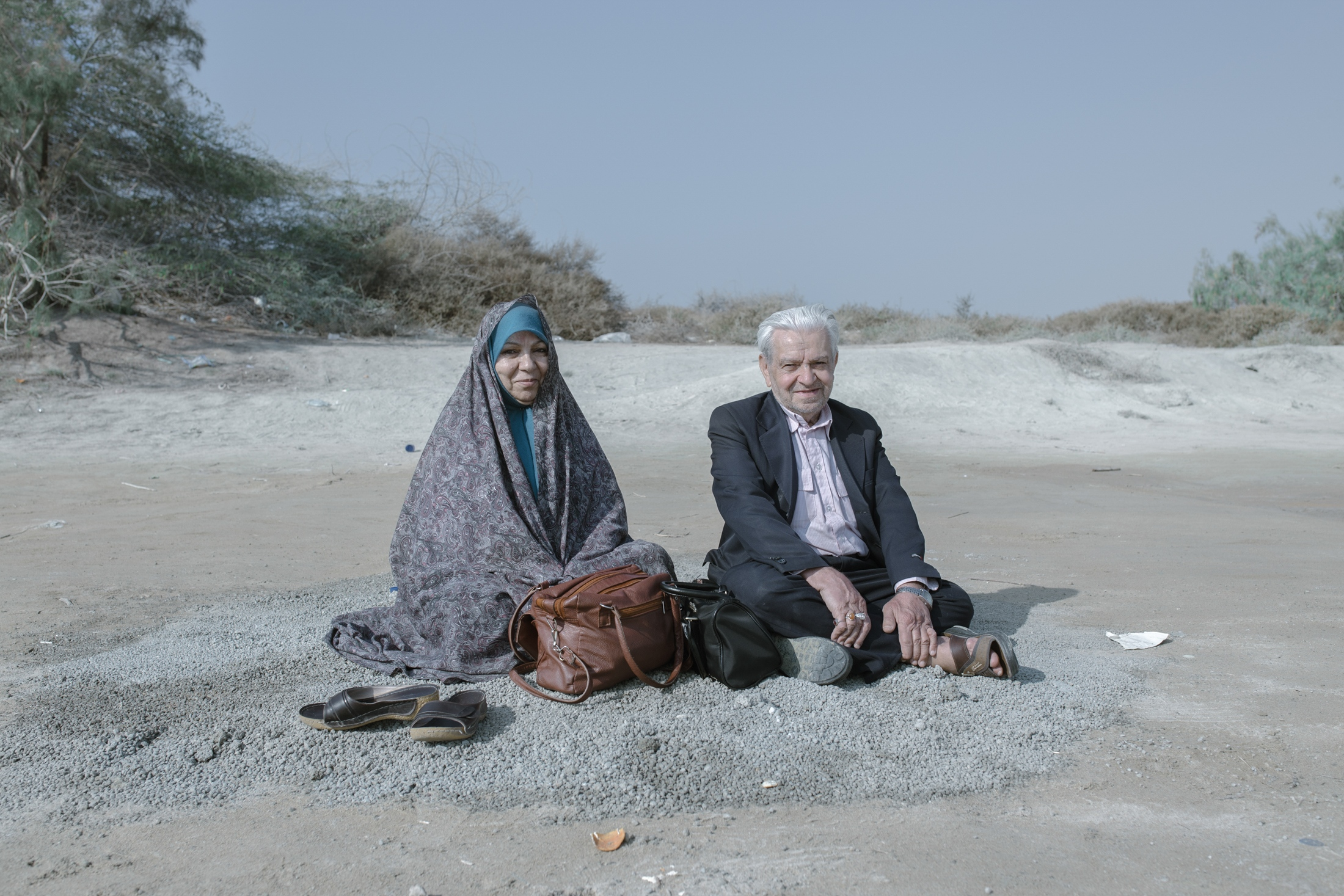 The couple rests on the coast of Pink lake(Lipar lake) in the Chabahar region. It is a free port (Free Trade Zone) on the coast of the Gulf of Oman. Sistan, as a distant and isolated province with the agriculture-dependent economy, dying up of the Hamun wetland have created difficulties for livelihoods Despite the scarcity of water sources, 2017 witnessed an increase in the number of tourists to Sistan and Baluchestan, which promised to bring in some solace for the tottering local economy in which 95% of people living under the poverty line. The main attractions were sectors that did not depend on water. However, it failed to effect a significant change. Balochistan province. Iran.2018