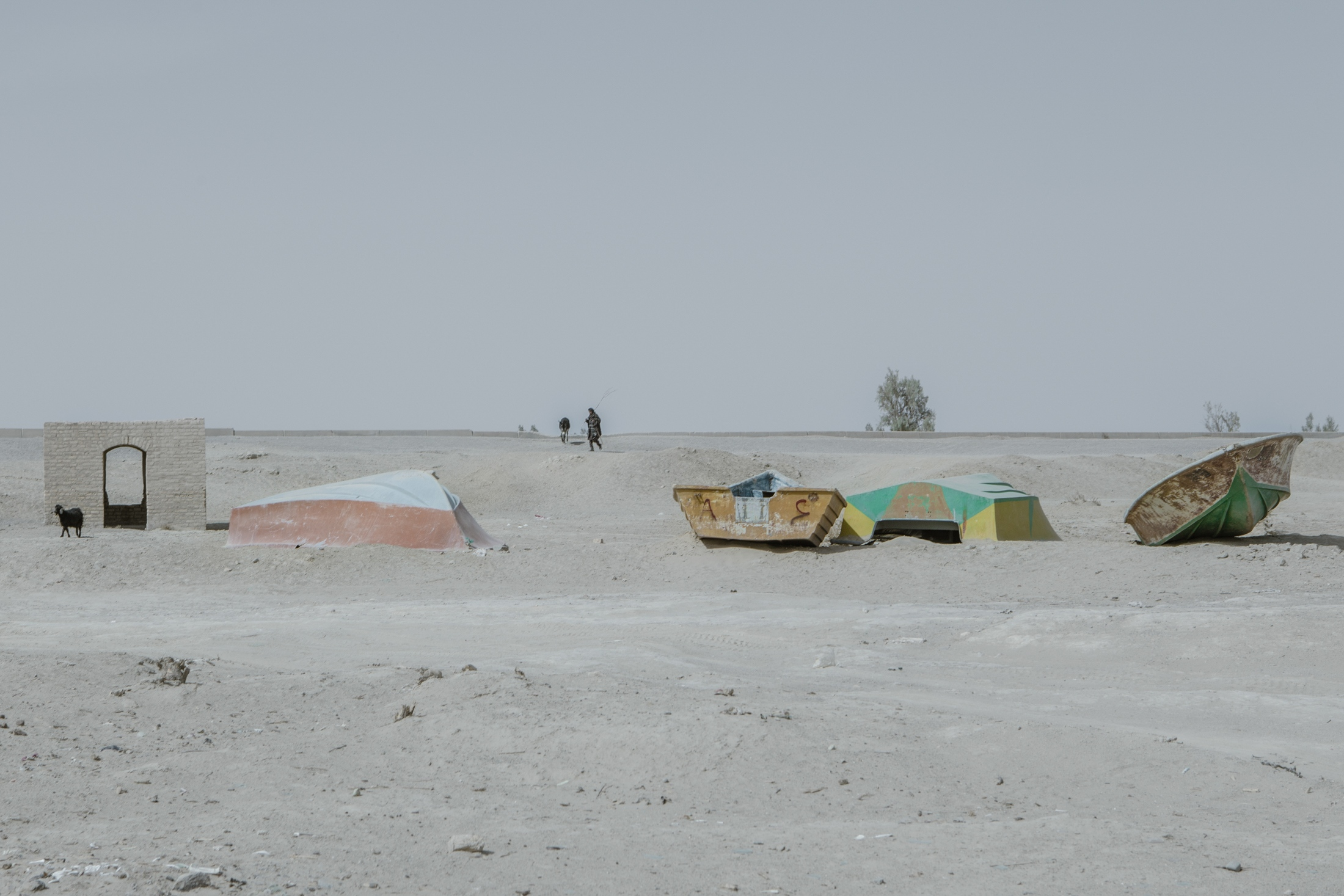 The broken and empty fishing boats are left here and there along the arid shore of Hamun-e Helmand in Qorqori Rural District.  As a distant and isolated province with an almost entirely agriculture-based economy, many families have migrated from the villages of Sistan to neighbouring provinces and regions due to 20 years of regional drought, climate change and the building of dams in neighbouring Afghanistan refusing to adapt to Iran's water rights. Qorqori Rural District.Sistan Province.Iran.2018