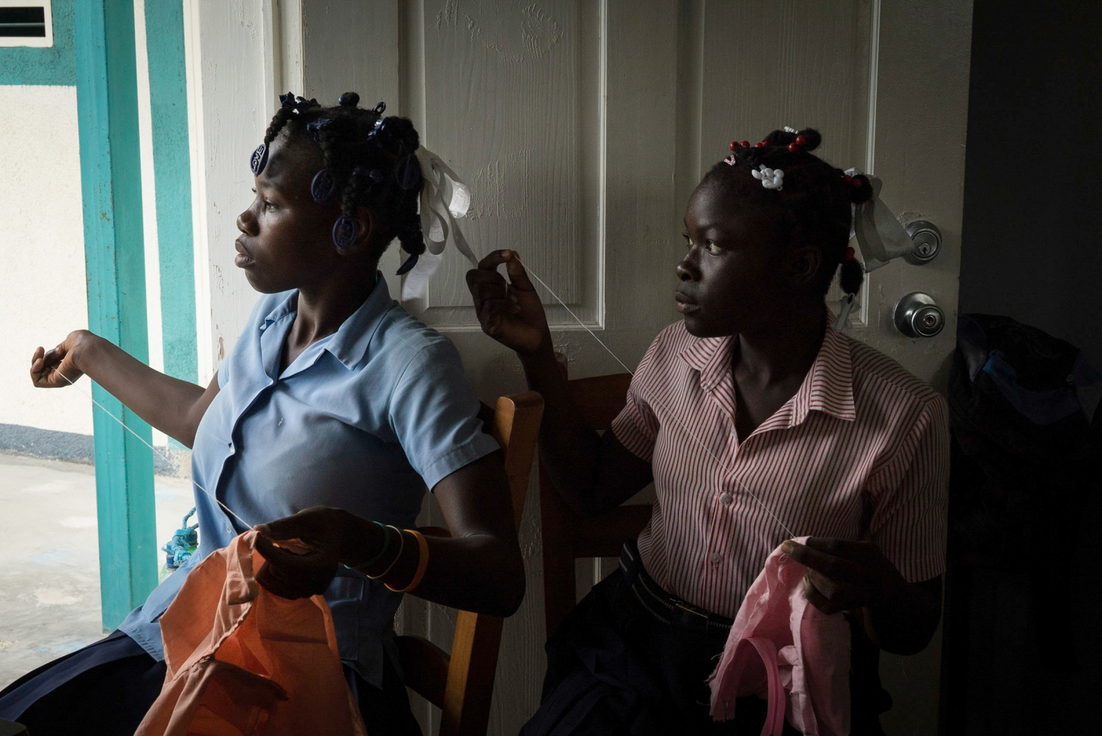 Faïka (left), 17, attends an afternoon sewing class. Since living in domesticity at her sister's home, Faïka has been able to attend school and learn a profession she can pursue once graduating. Since 2014, the Support Service for Professional Integration helps young graduates find jobs through trainings, internships, and partnerships with various companies. Only a small percentage of students, however, are able to find sustainable employment.