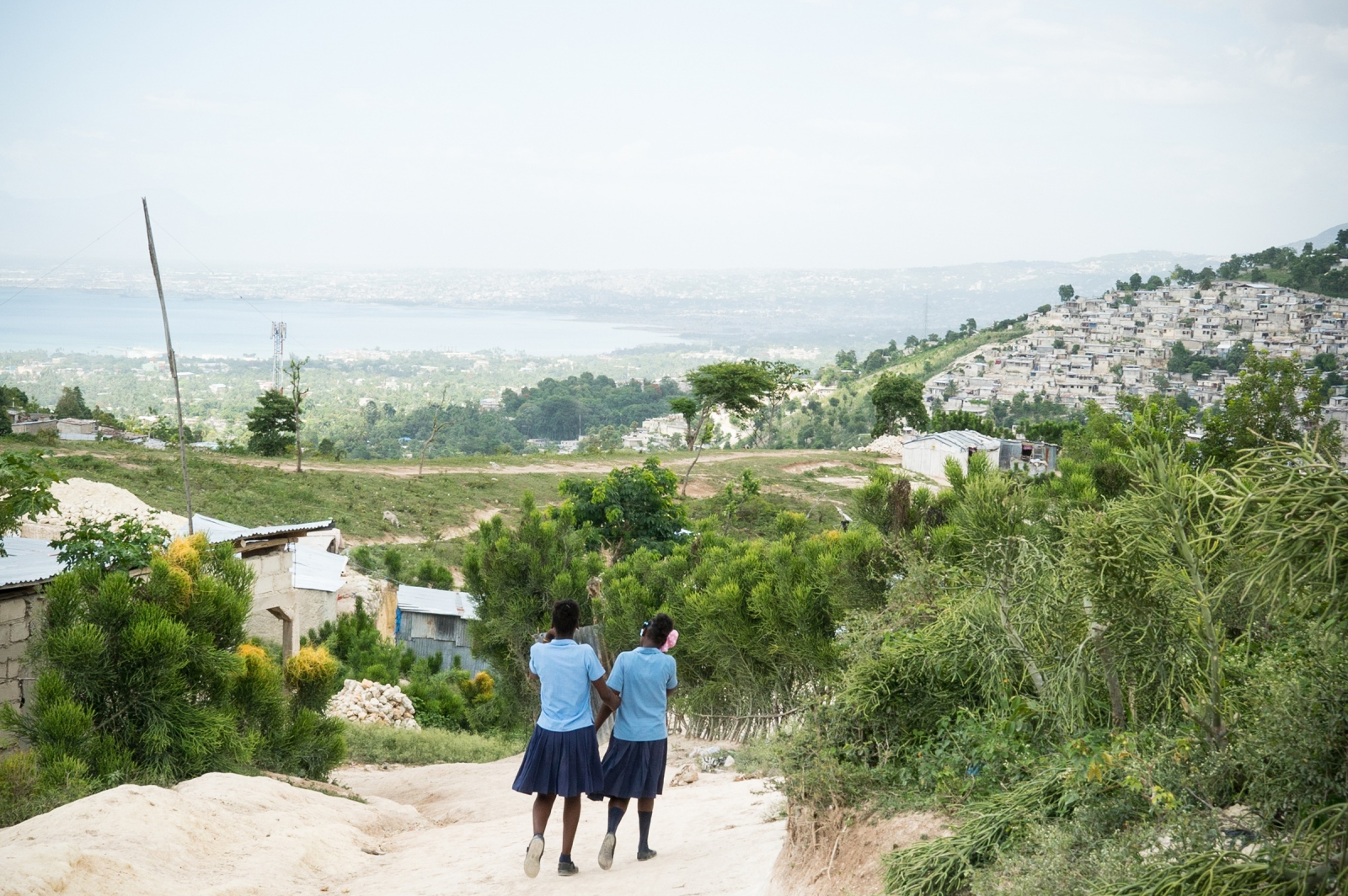 Faïka walks home with a friend after school. She is one of the 300 students - mostly current and former domestic children - of the Foyer Maurice Sixto school who attend class in the morning and learn a profession in the afternoon. The school's founding priest, Father Miguel Jean-Baptiste, opened its doors in 1989. His initiative tackled a staggering reality: a quarter of the children who live separated from their families don't go to school.