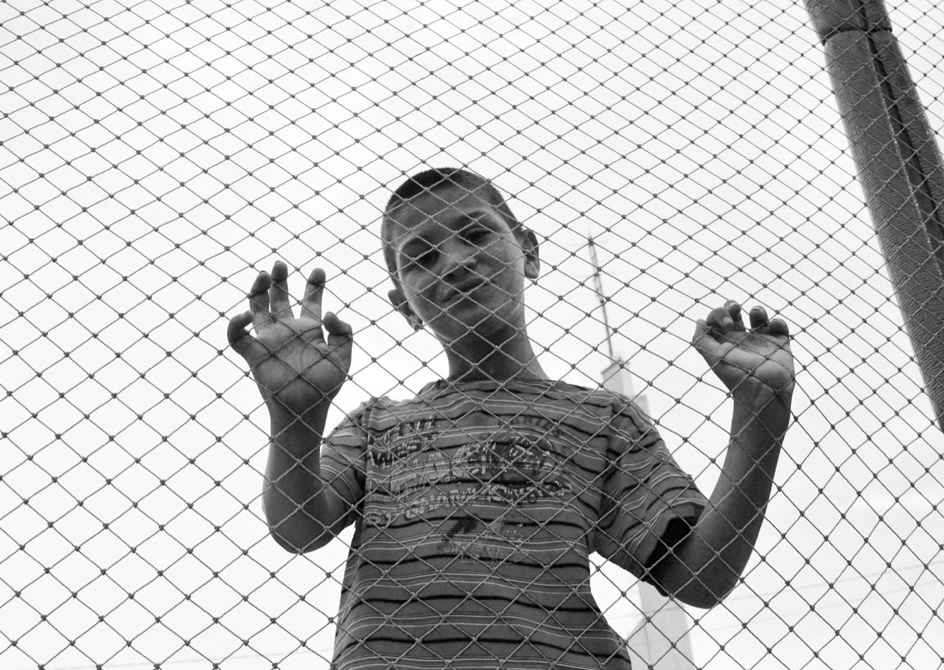 A young boy looks through a fence in ethnically divided city of Mitrovica, in northern Kosovo, August 2018