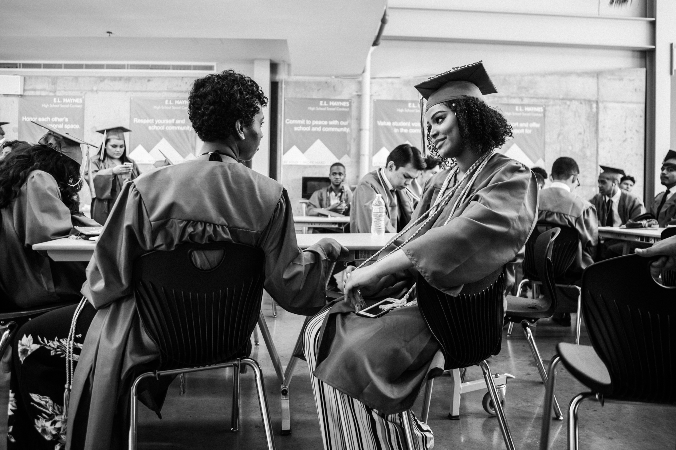 """Dasani Watkins chats with her friend at E.L. Haynes High School on June 16, 2018, before going to Howard University for her graduation ceremony. """"I approached my high school career as if it were a race to college…All I wanted to do was escape the life of poverty, to not become a statistic in a world that sees all black people as lazy, as our president proclaims. Fear of failure guided my approach. I was a hare trying to win a race,"""" says Watkins. Watkins graduated as the salutatorian of her high school."""