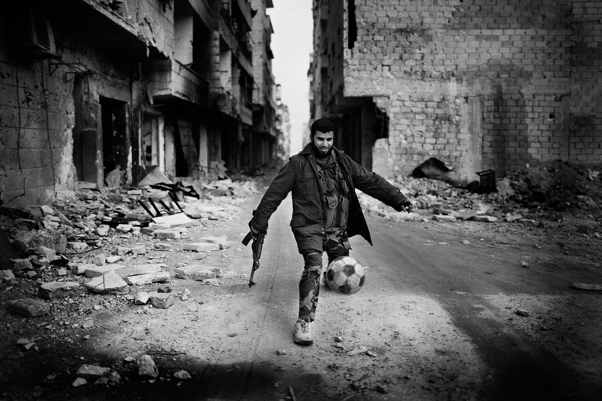 "A Syrian islamist rebel plays football in the Al-Amriyah neighborhood of Aleppo, Syria, Wednesday, Jan. 2, 2013. The United Nations estimated that more than 400,000 people have been killed in Syria's 60-month-old uprising against authoritarian rule, a toll one-third higher than what anti-regime activists had counted. The U.N. human rights chief called the toll ""truly shocking."" Copyright: Spanish Photojournalist Andoni Lubaki"