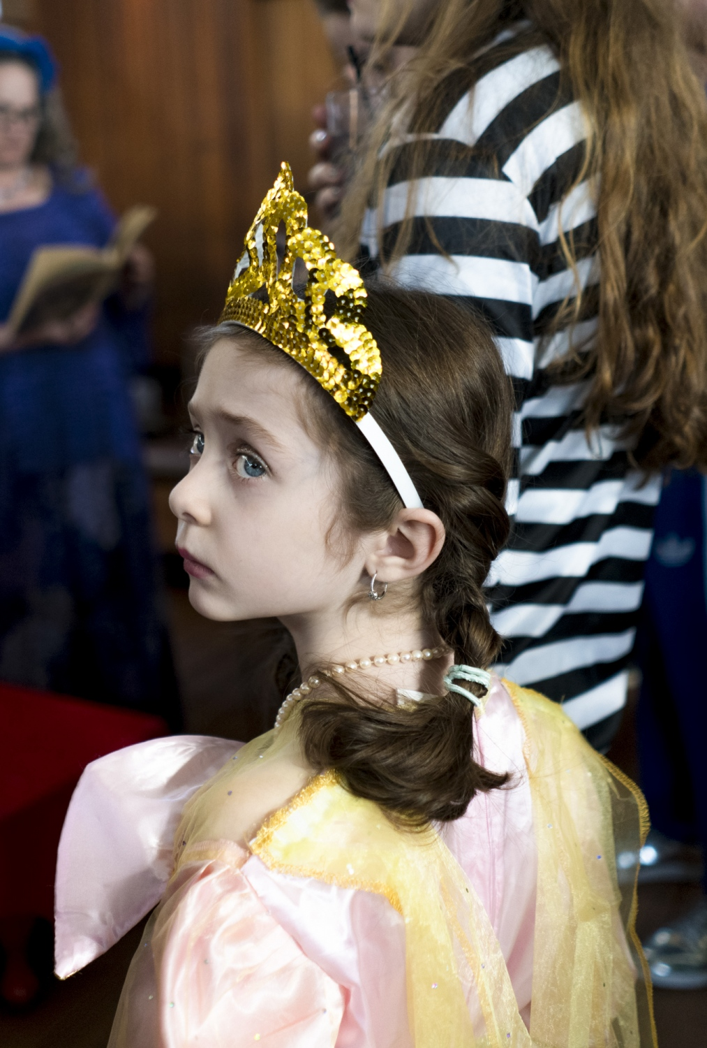 A young girl dressed as Esther listens to a reading of the Megillah at a Chabad Lubavitch party in the Chelsea neighbourhood of Manhattan. Children and adults dress up during Purim to celebrate the saving of the Jews from the evil figure of Haman who plotted against them.