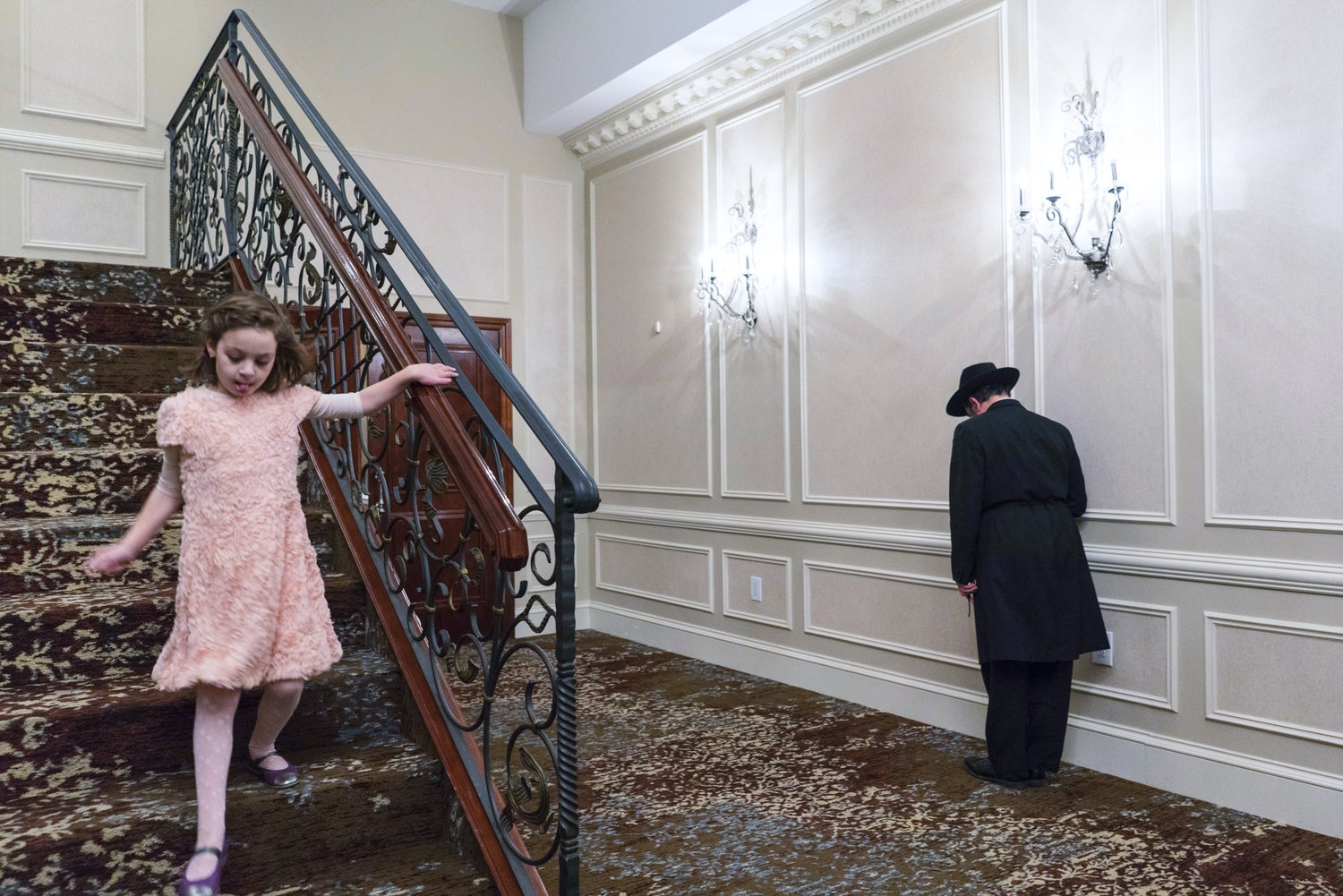 A young girl descends a flight of stairs at the Rachik's wedding reception while an older guest prays in the hallway, Crown Heights, Brooklyn.
