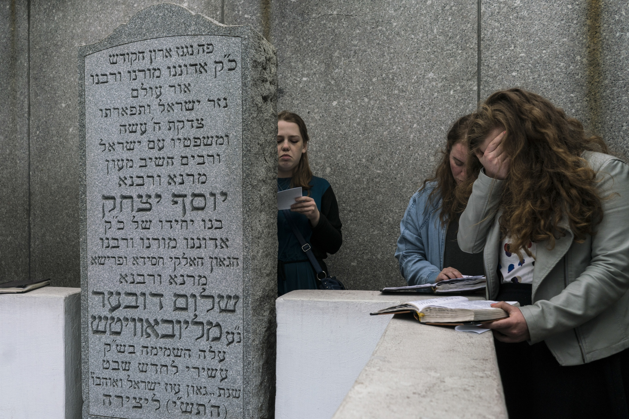 Lubavitchers pray at the Rebbe's tomb at the Chabad Lubavitch Ohel, Queens NY. Visitors leave slips of paper with written prayers on top of his grave.