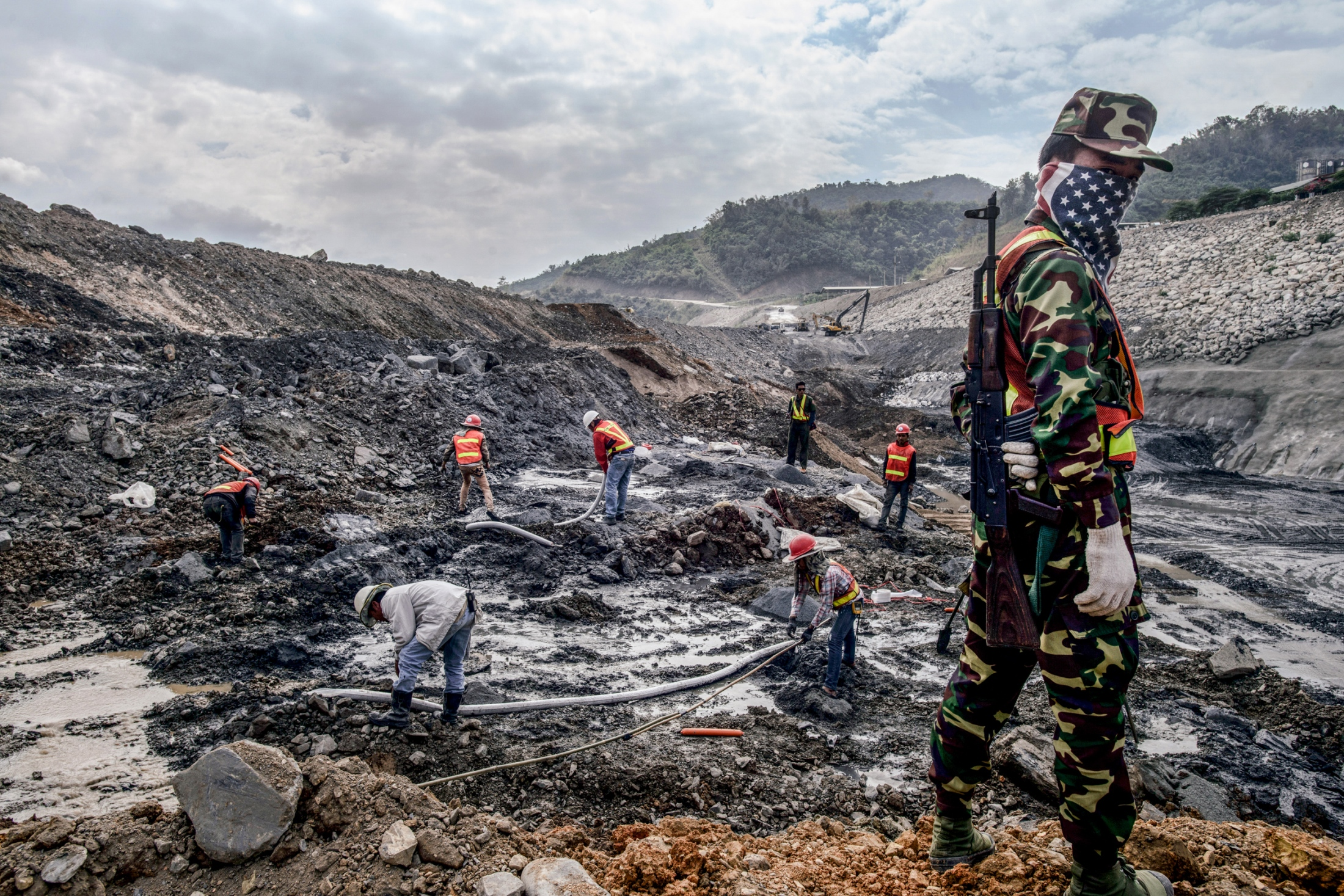 A Lao soldier is guarding a construction worker placing flash powder for exploding rocks for the Dam construction and other parts of the dam including a reservoir length of 60 to 100km, the forest in the area alongside the riverbank will be destroyed. December 16, 2014.