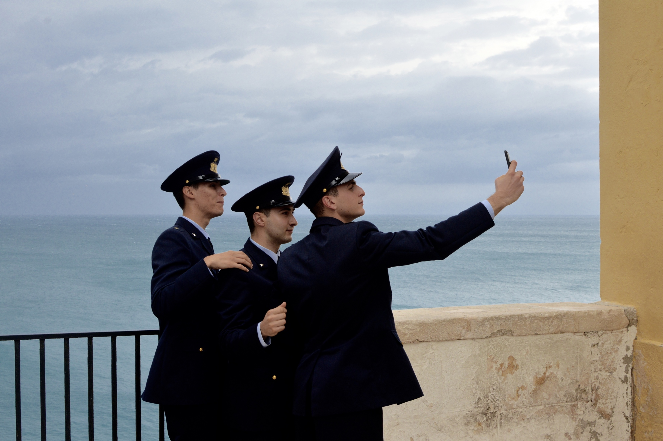 A group of young sailors stops by a panorama point to take a selfie in Polignano a Mare, Italy, November 2018
