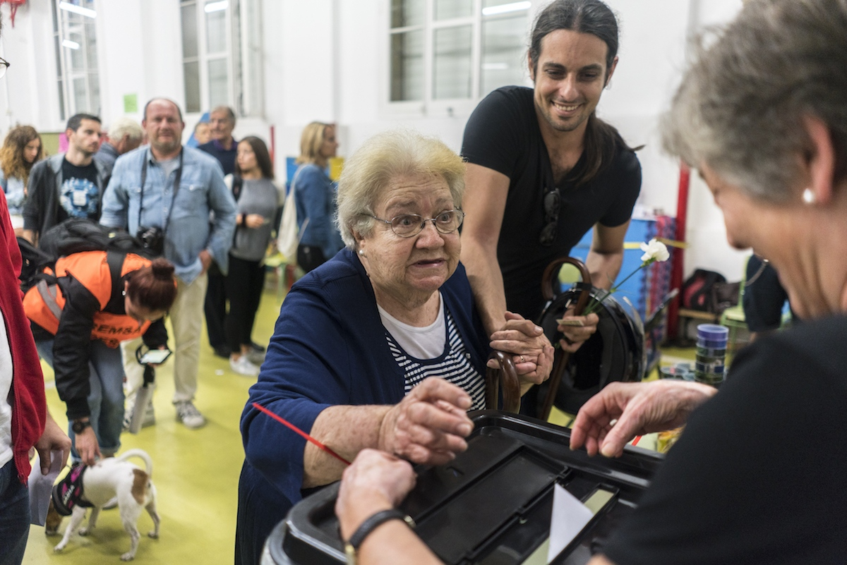 """Having just met outside the voting center, Victor helped walk Magda through the crowd and to the voting tables. """"I saw her outside struggling, and because I myself don't have a grandmother to help, I said, today Magda will be my grandmother""""."""