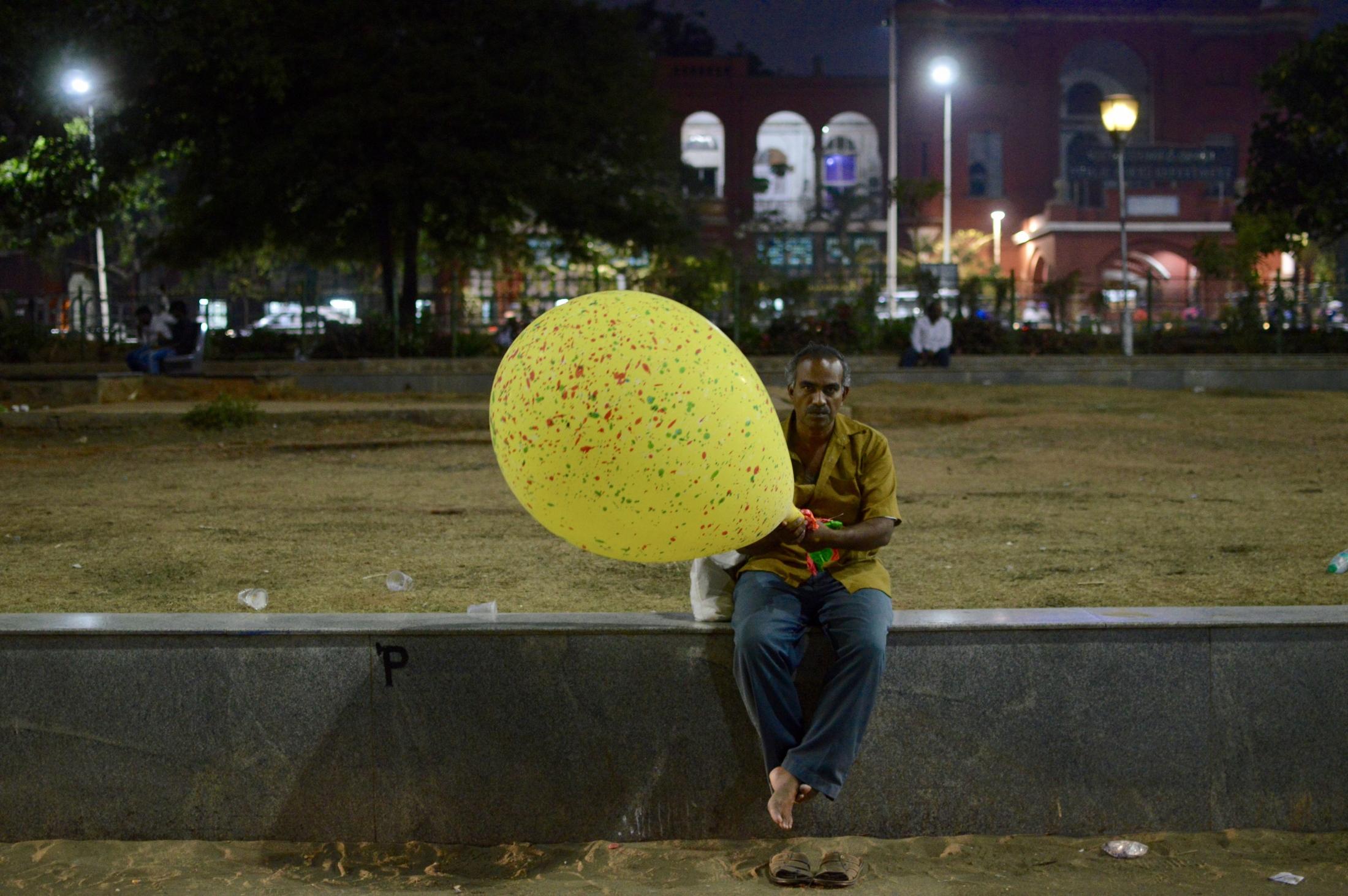 A street vendor carries a balloon as he sits on a platform overlooking the 12-km-long beach of Chennai, Tamil Nadu, June 2017