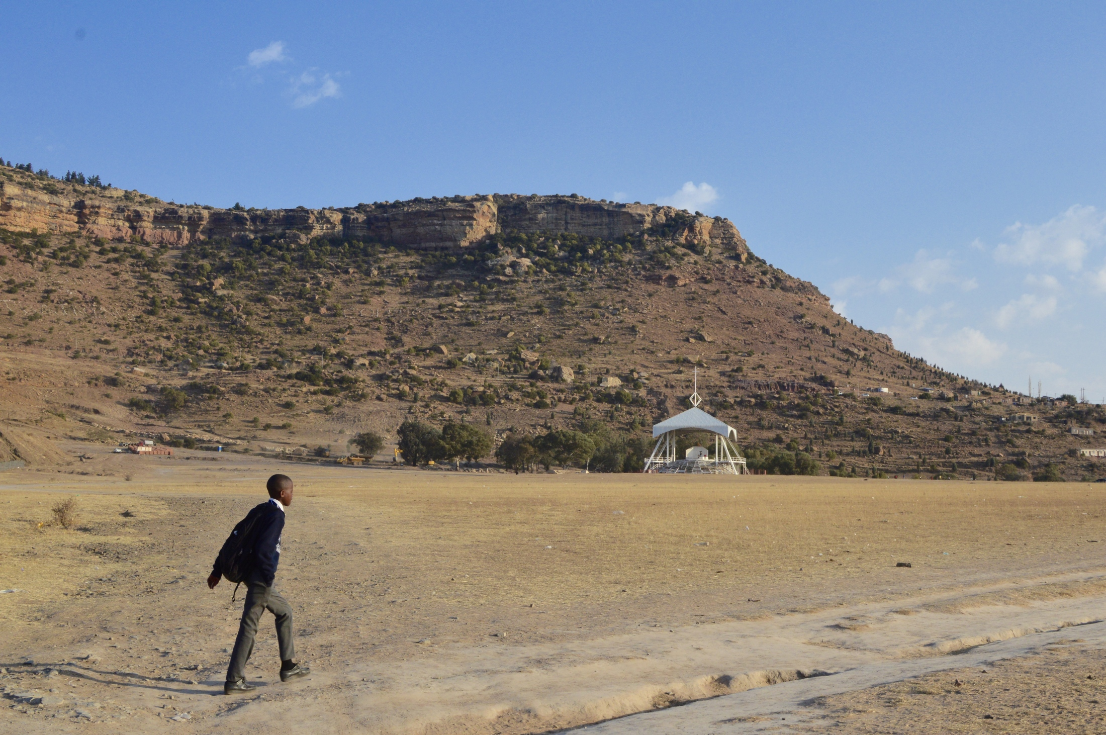 A shoolboy walks across a field where Pope John Paul II celebrated a mass during his two-day visit to the country in 1988, Maseru, Lesotho, July 2017