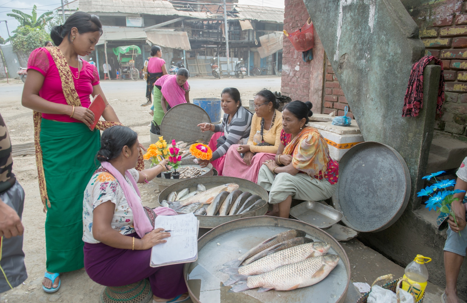 Fisherwomen and vegetable vendors wrap up business for the day in the Ema market in Ningthoukhong, in Manipur. Recurrent floods during monsoon season in 2017 impacted fisheries and vegetable harvest in the area.